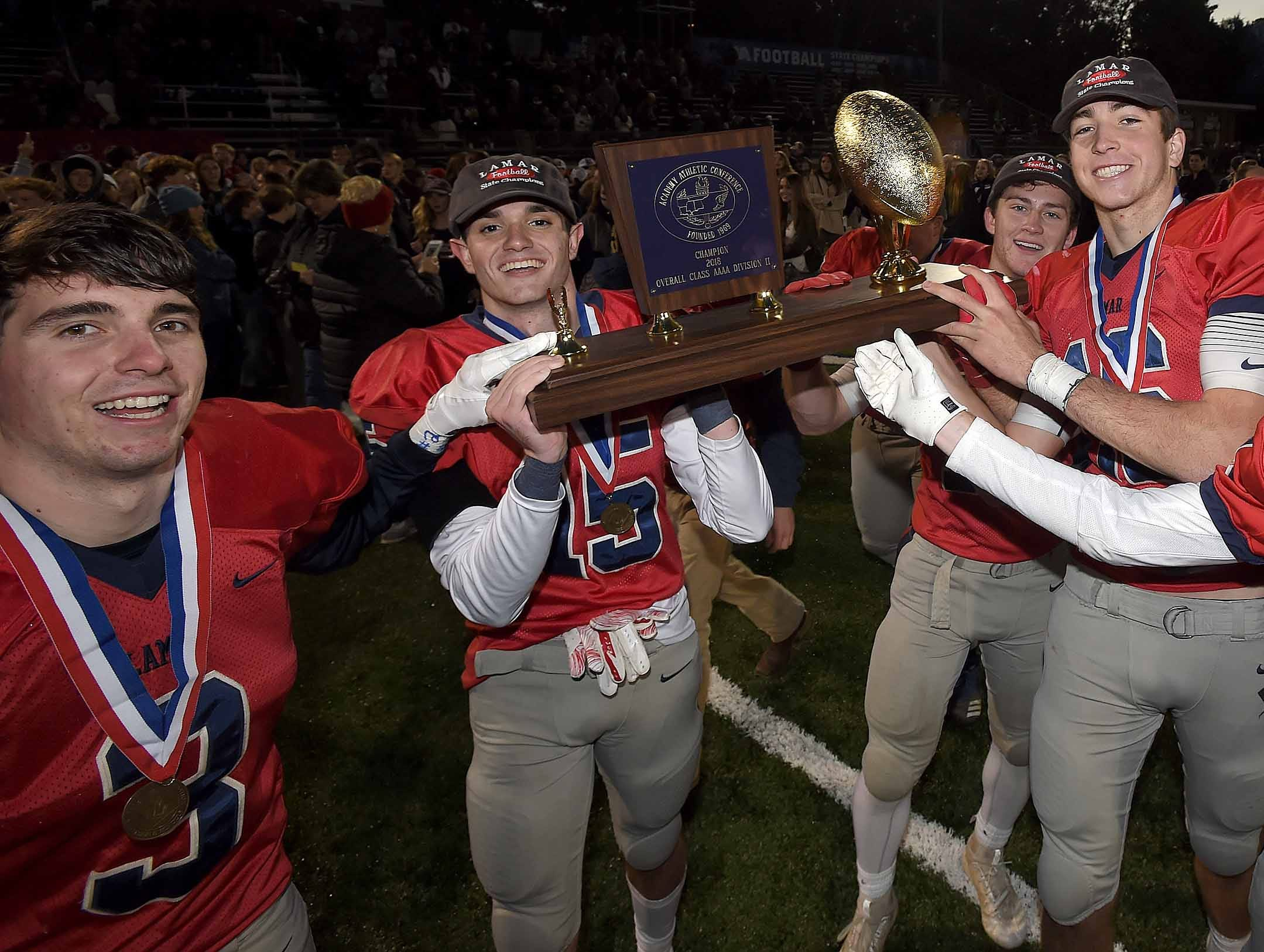 The Lamar School Raiders celebrate with the trophy after beating Simpson Academy on Thursday, November 15, 2018, in the MAIS Class AAAA-D2 Football Championship at Jackson Academy in Jackson, Miss.