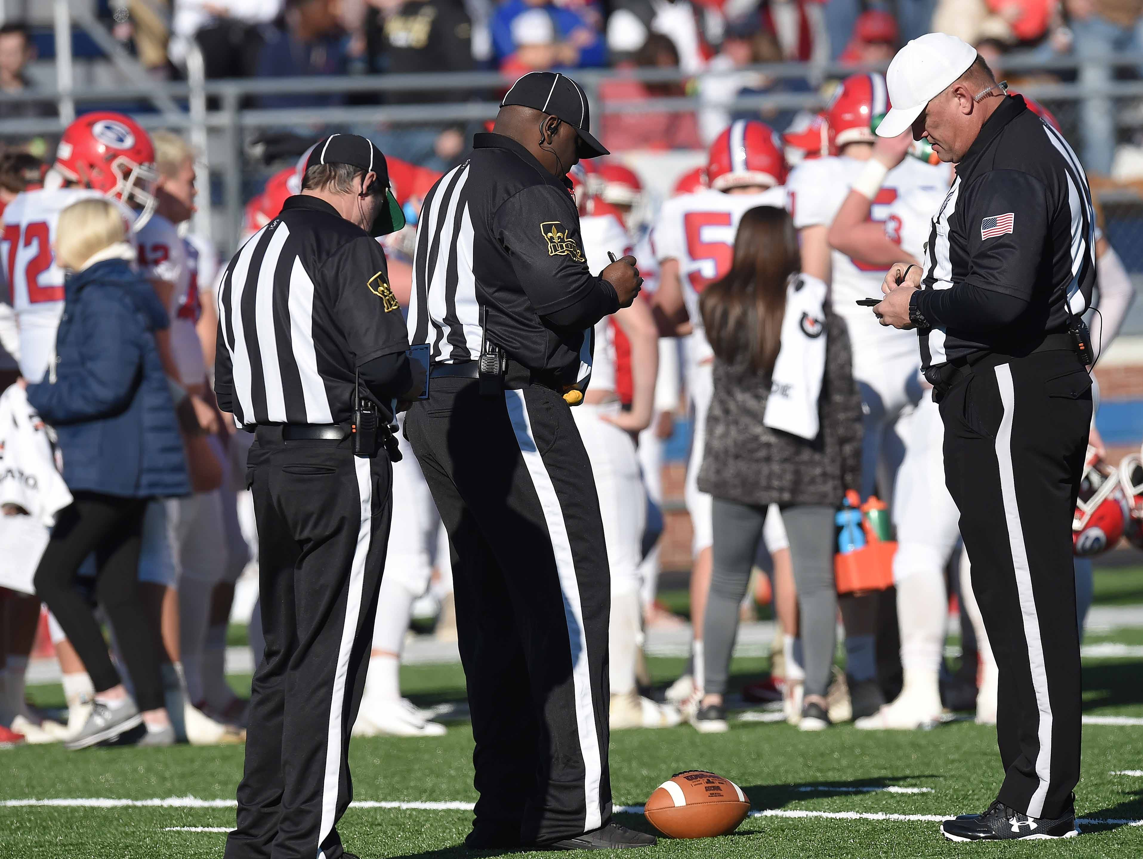 Officials catch up on their notes during a time out on Thursday, November 15, 2018, in the MAIS Class AAAA-D2 Football Championship at Jackson Academy in Jackson, Miss.