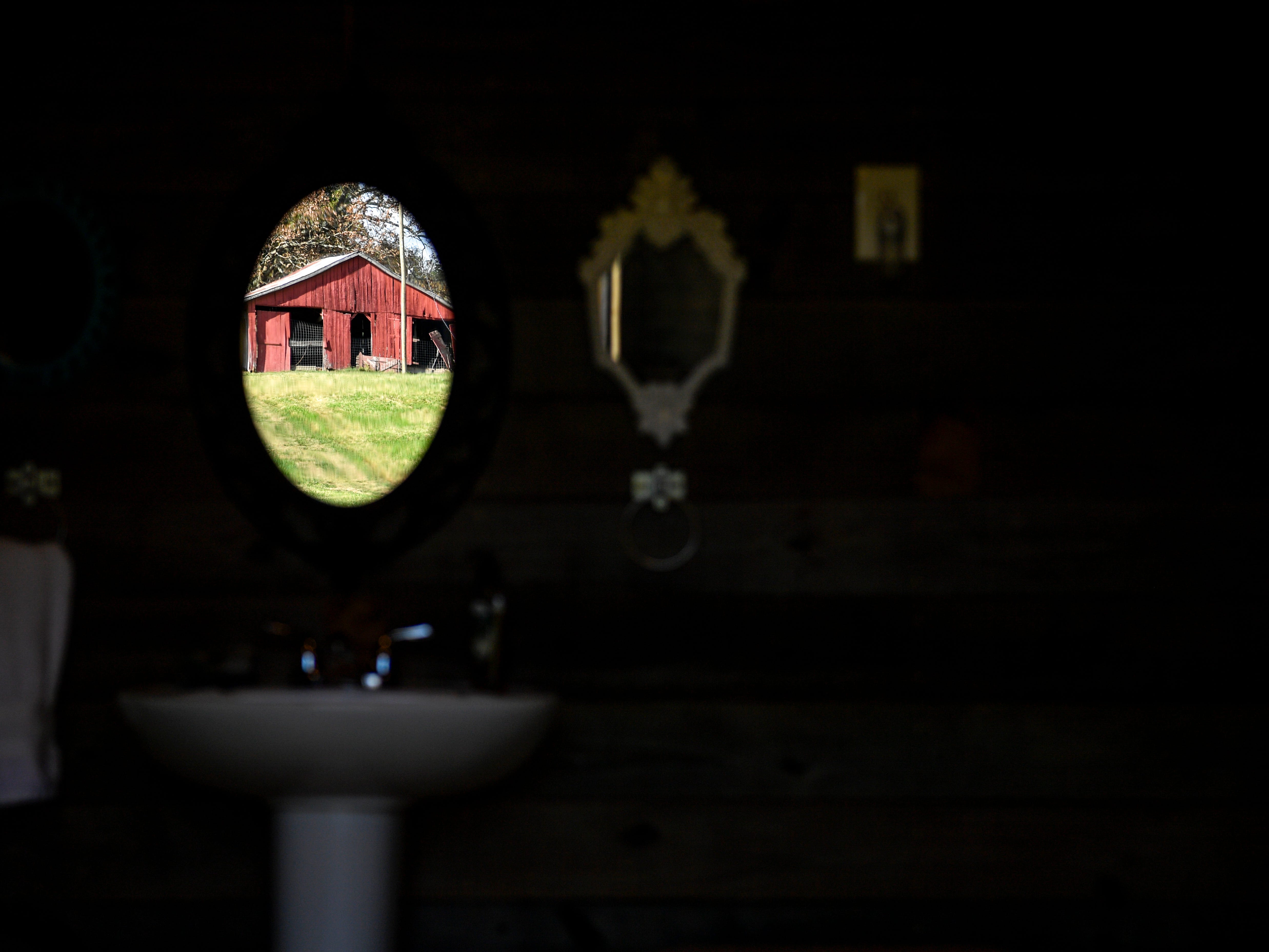One of the barns on the Pitoni's farm can be seen in the reflection of a mirror in the outdoor bathroom at Stillwaters Farm in Henderson, Tenn., on Monday, Nov. 5, 2018.