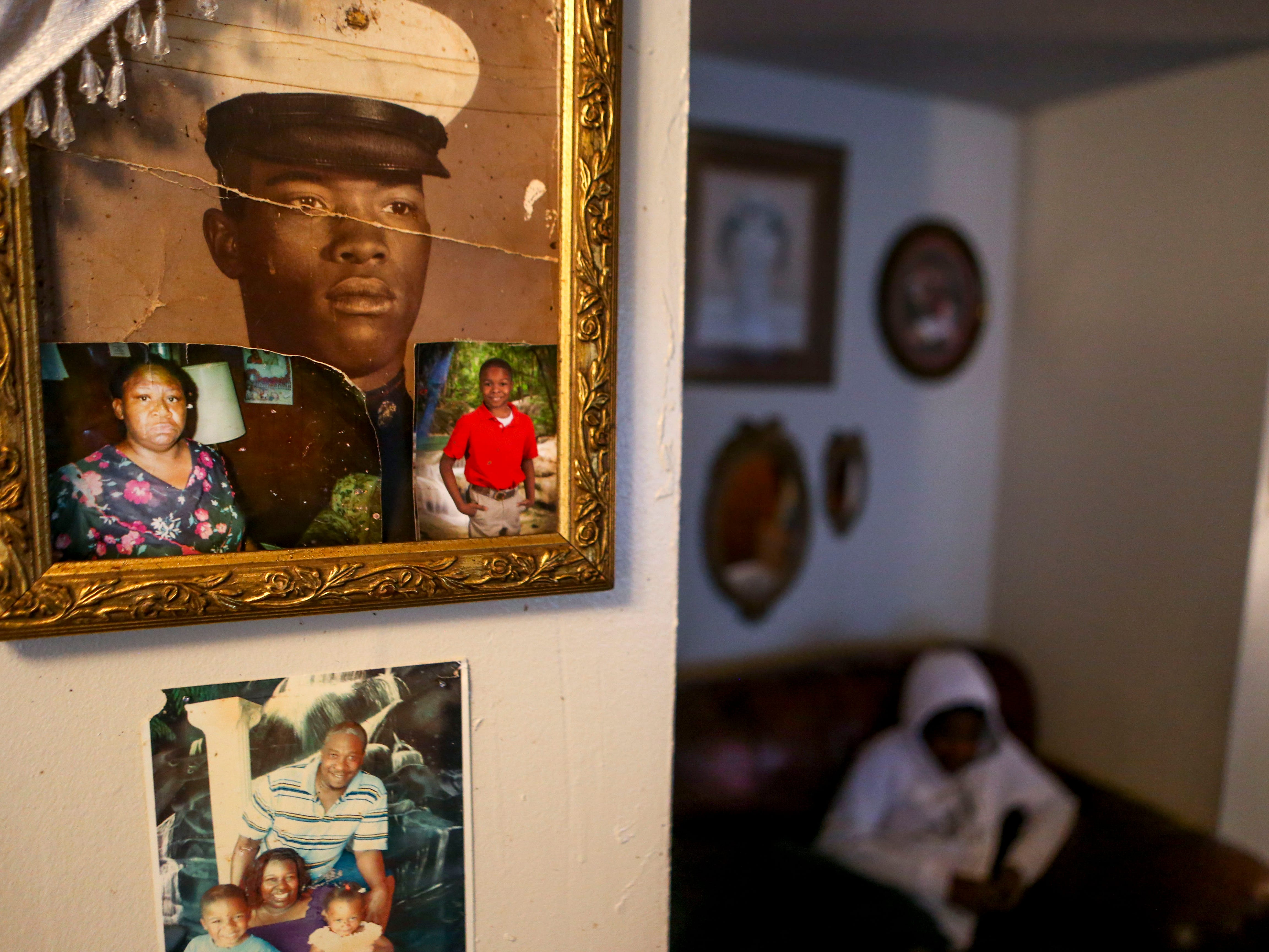 Portraits of family members are mounted above a photo of the McCurry family at their home in Guardian Courts Apartments in Jackson, Tenn., on Tuesday, Oct. 23, 2018.