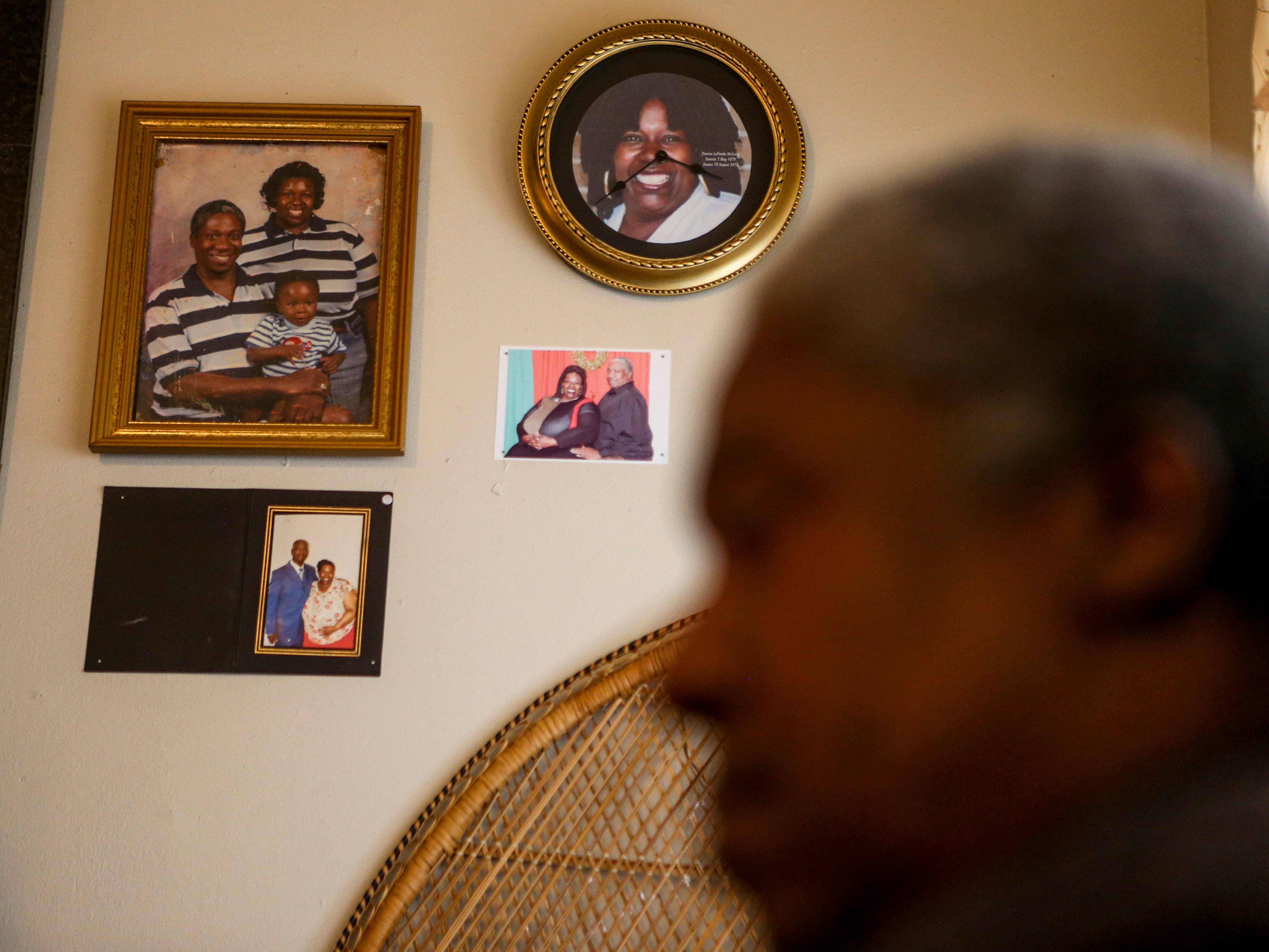Family portraits and a clock with the face of Jimett McCurry adorn the walls at the McCurry's home in Guardian Courts Apartments in Jackson, Tenn., on Tuesday, Oct. 23, 2018.