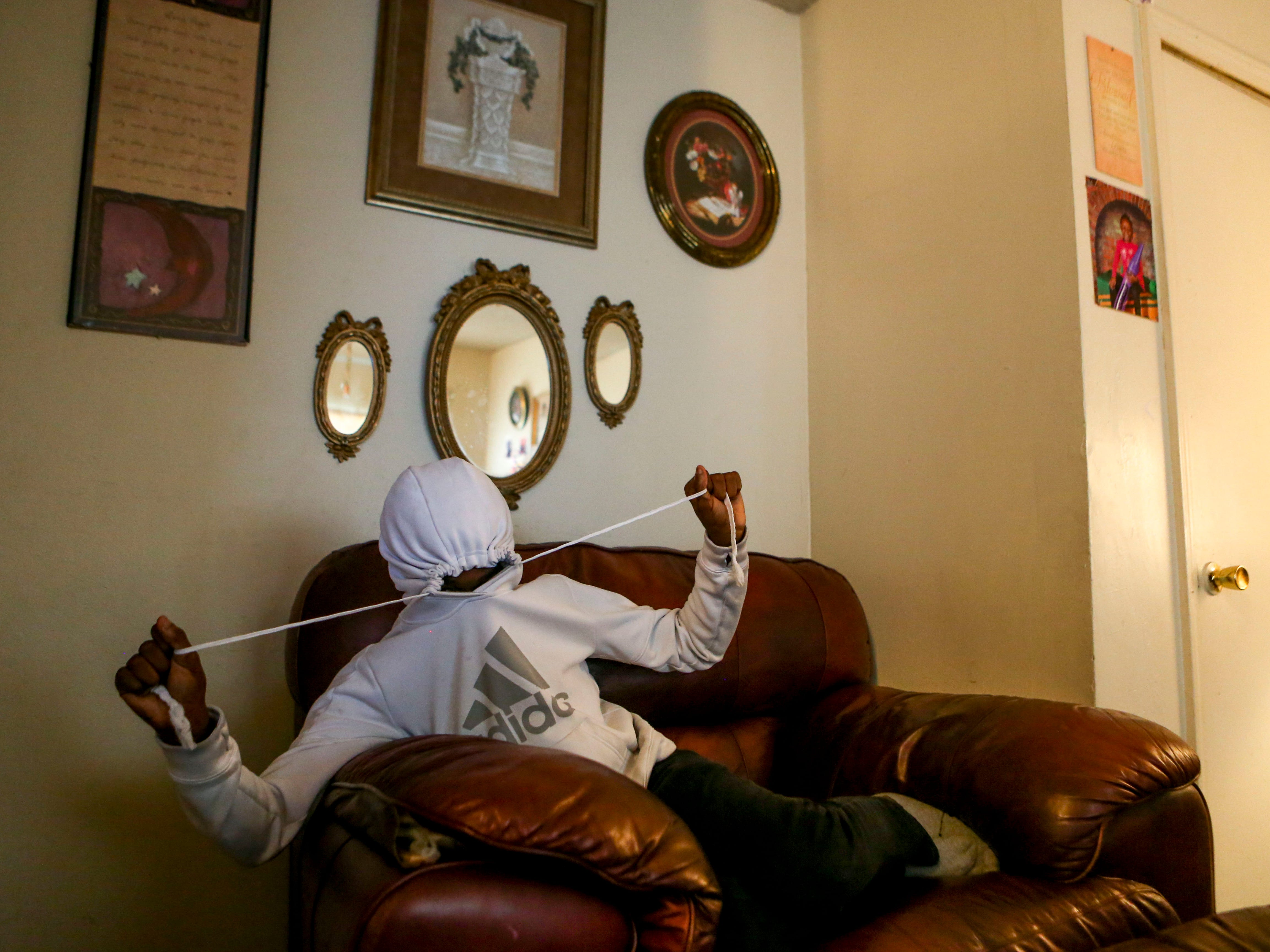 Niarobi McCurry, 11, tightens the string on his hoodie while hanging out on the couch at the McCurry's home in Guardian Courts Apartments in Jackson, Tenn., on Tuesday, Oct. 23, 2018.