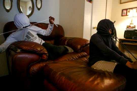 Niarobi McCurry, 11, left, and Keyonce McCurry, 13, right, pull their jacket's hoods tight around their heads while sitting the couch at the McCurry's home in Guardian Courts Apartments in Jackson, Tenn., on Tuesday, Oct. 23, 2018.