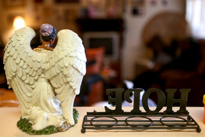A statue of an angel and a candle platform can be seen looking over the family room at the McCurry's home in Guardian Courts Apartments in Jackson, Tenn., on Tuesday, Oct. 23, 2018.