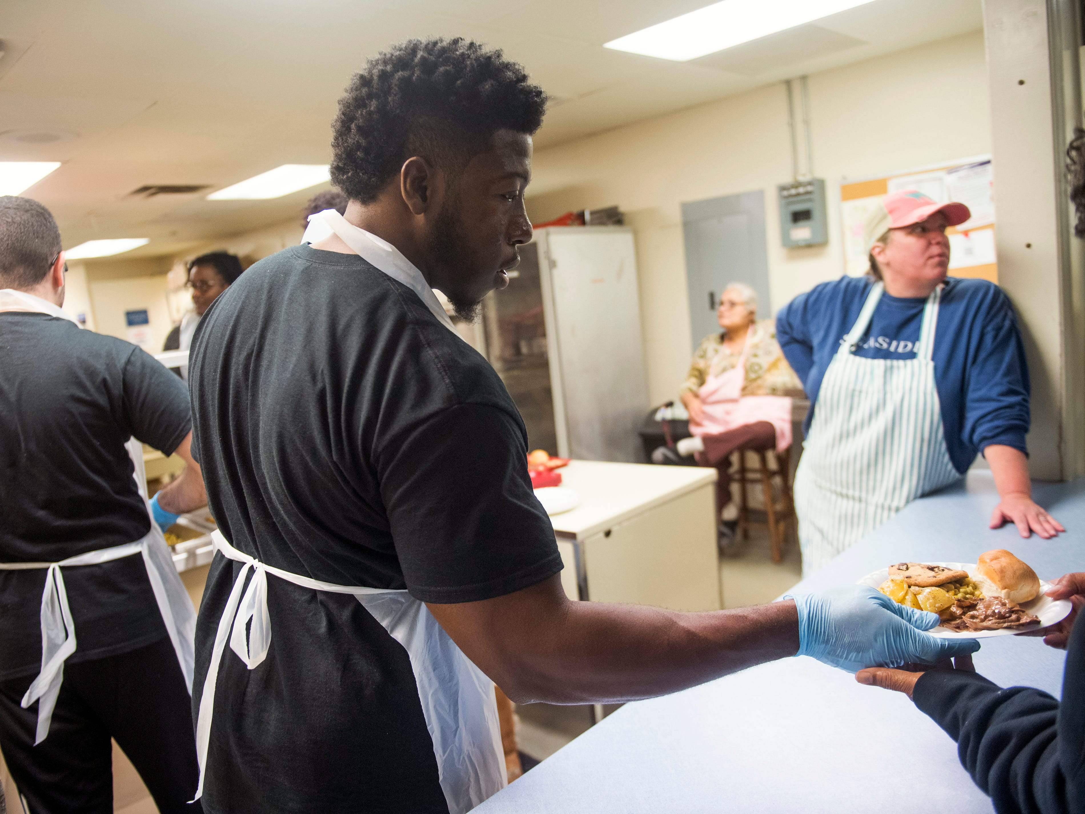 Chuck Ejimadu, a Phi Delta Epsilon medical fraternity member from Ross University School of Medicine, hands out a plate of food at The Love Kitchen in Knoxville on Wednesday, November 14, 2018.