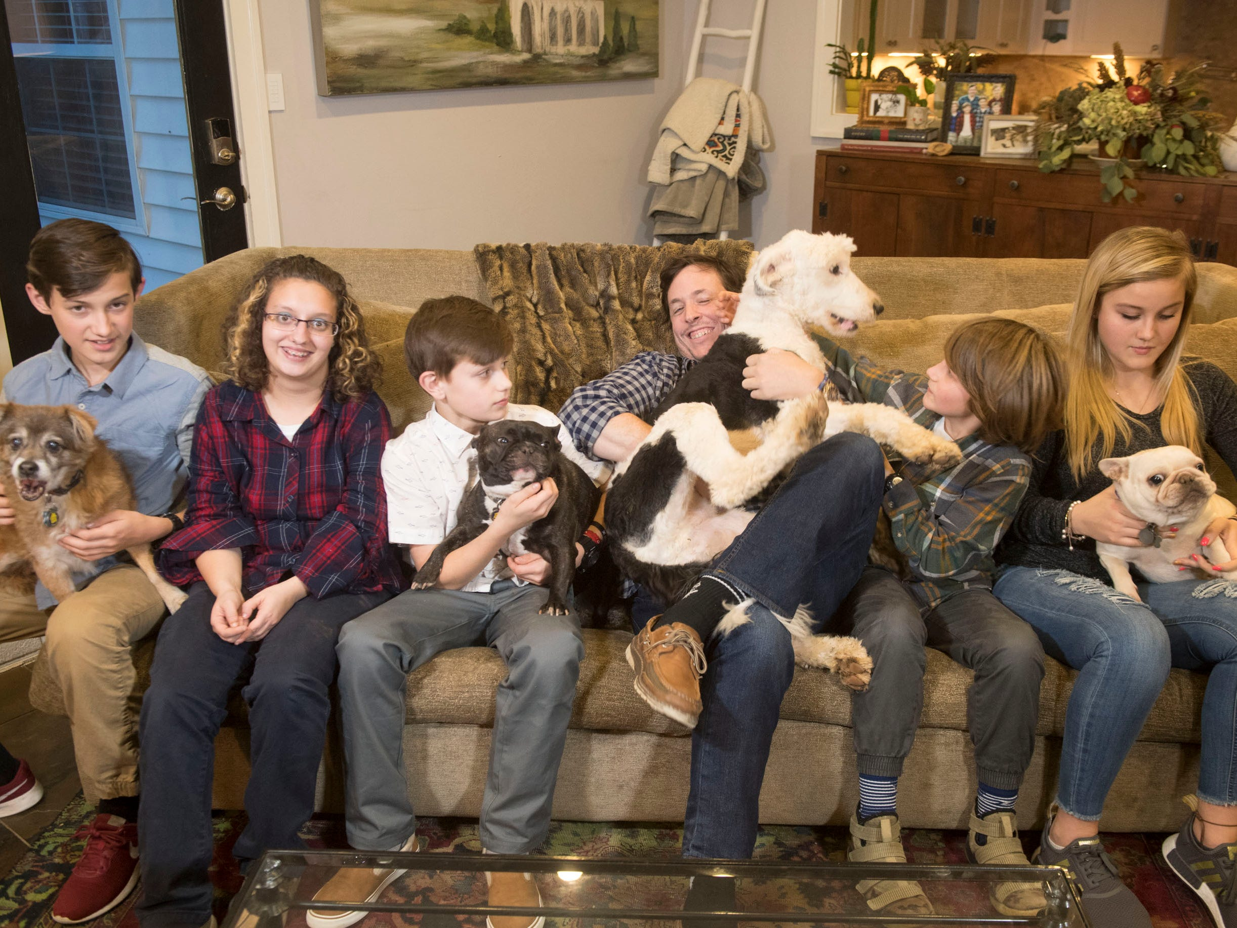 Things are hectic these days in Simon Hall's household. From left, Nick holds Stella, next is Lexi, Blake holds Sherlock, Hall tries to wrangle Mr. Pickles, Mason sits next, and Abby holds Sprout.