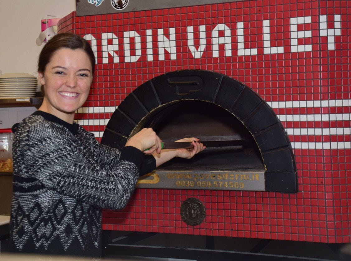 General Manager Grace McMichael flashes a thousand watt smile as she runs a brush over the oven floor to keep wood ash from getting on the pizzas at Hard Knox Pizza.