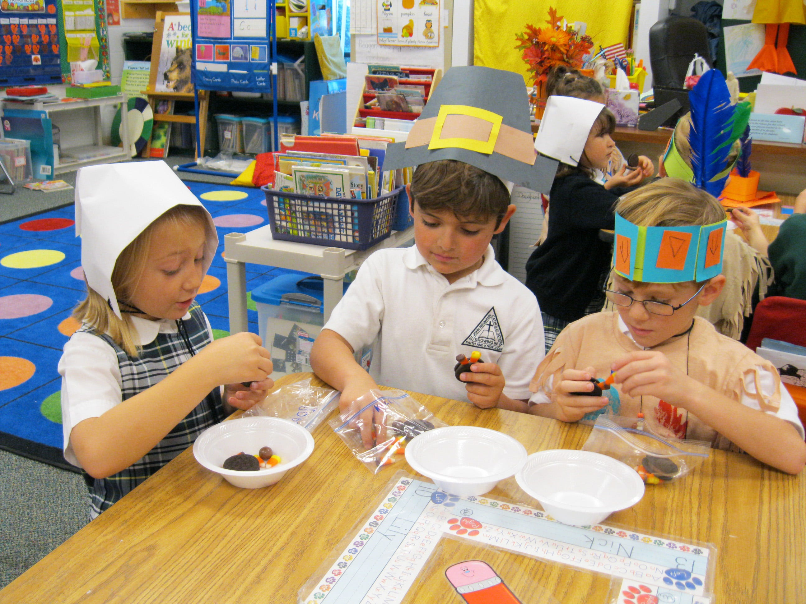The kindergarten and first grade students at St. John Neumann Catholic School celebrated Thanksgiving by dressing as Native Americans and pilgrims, eating lunch, playing, singing and praying together. From left, Josephine Kelley, Nicky Molino and Nick Gerkins create turkeys together.
