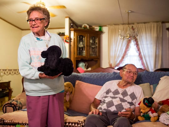 Phil Candia, left, shows off her plush dog Blackie as her husband Whorley Candia, right, sits at their home in Newport on Friday, November 2, 2018.