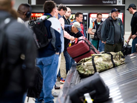 Arriving passengers pick up their luggage at baggage claim at McGhee Tyson Airport on Friday, November 16, 2018.