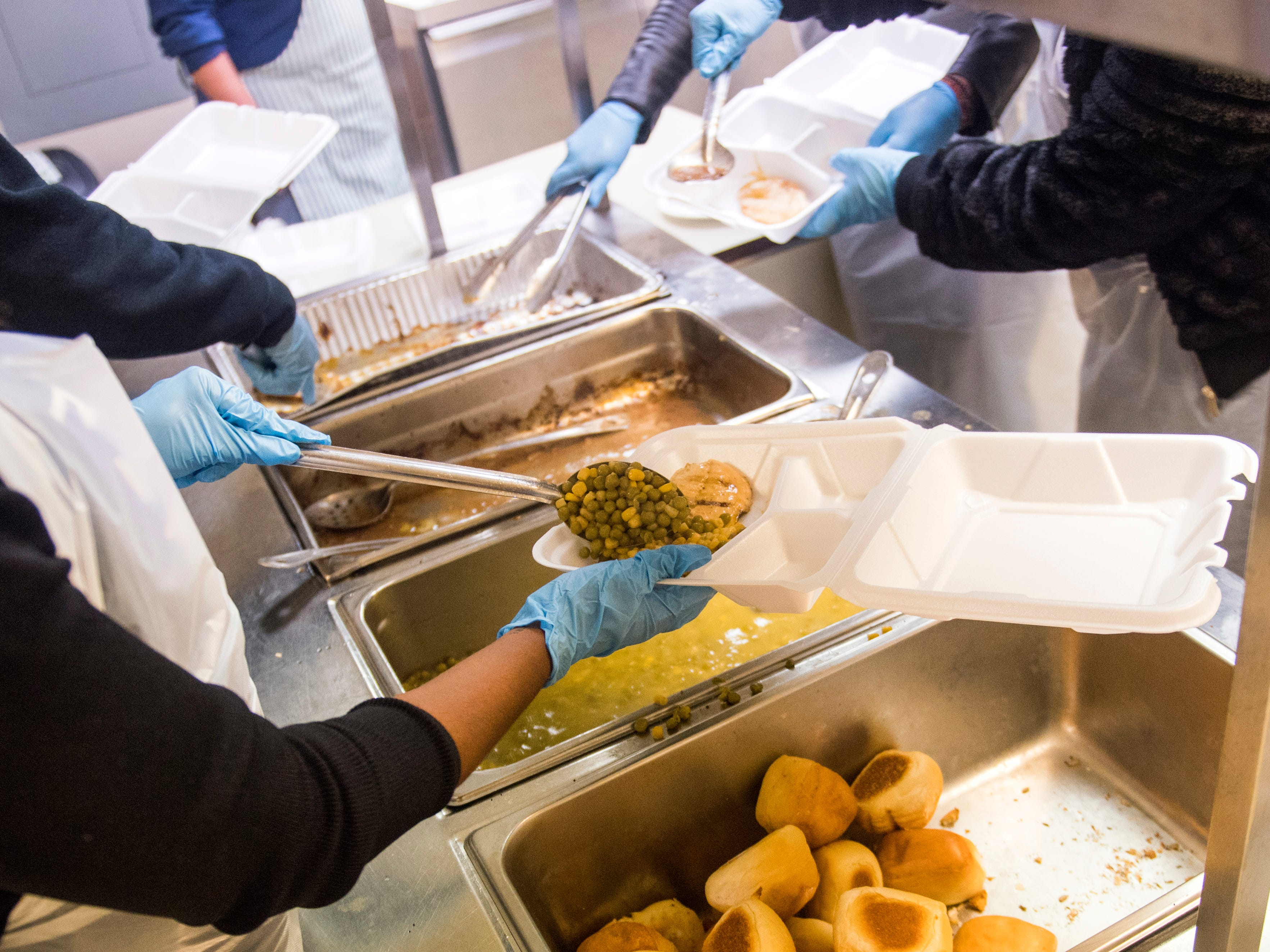 Phi Delta Epsilon medical fraternity members from Ross University School of Medicine prepare plates of food at The Love Kitchen in Knoxville on Wednesday, November 14, 2018.