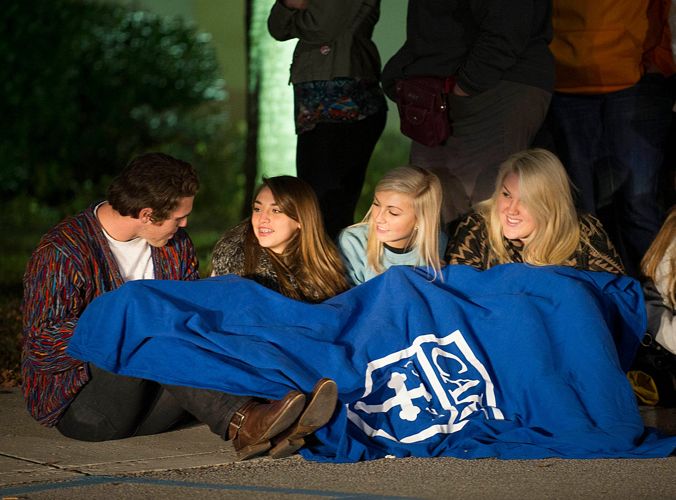 Webb School students Scott Nord, left, sisters Marya and Maya Zaouk, and Jessica Unkefer pass the time as they wait for the doors to open for the Belk Thanksgiving Day sale on Thursday, Nov. 28, 2013, at West Town Mall. They are under a CAK blanket loaned by a friend.
