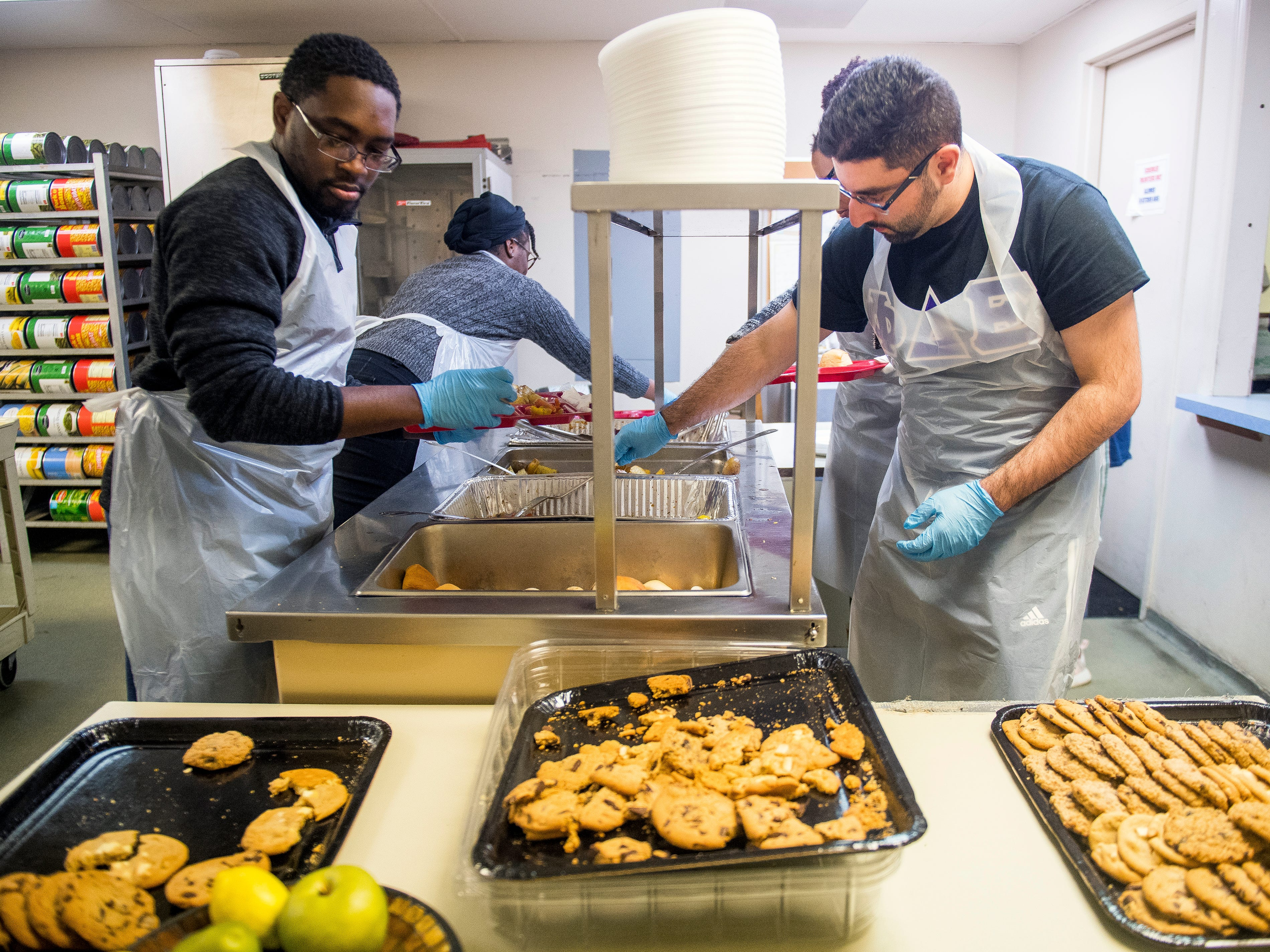 Nanakwame Darkwa, left, and Haaris Siddiq, right, Phi Delta Epsilon medical fraternity members from Ross University School of Medicine, prepare plates of food together at The Love Kitchen in Knoxville on Wednesday, November 14, 2018.