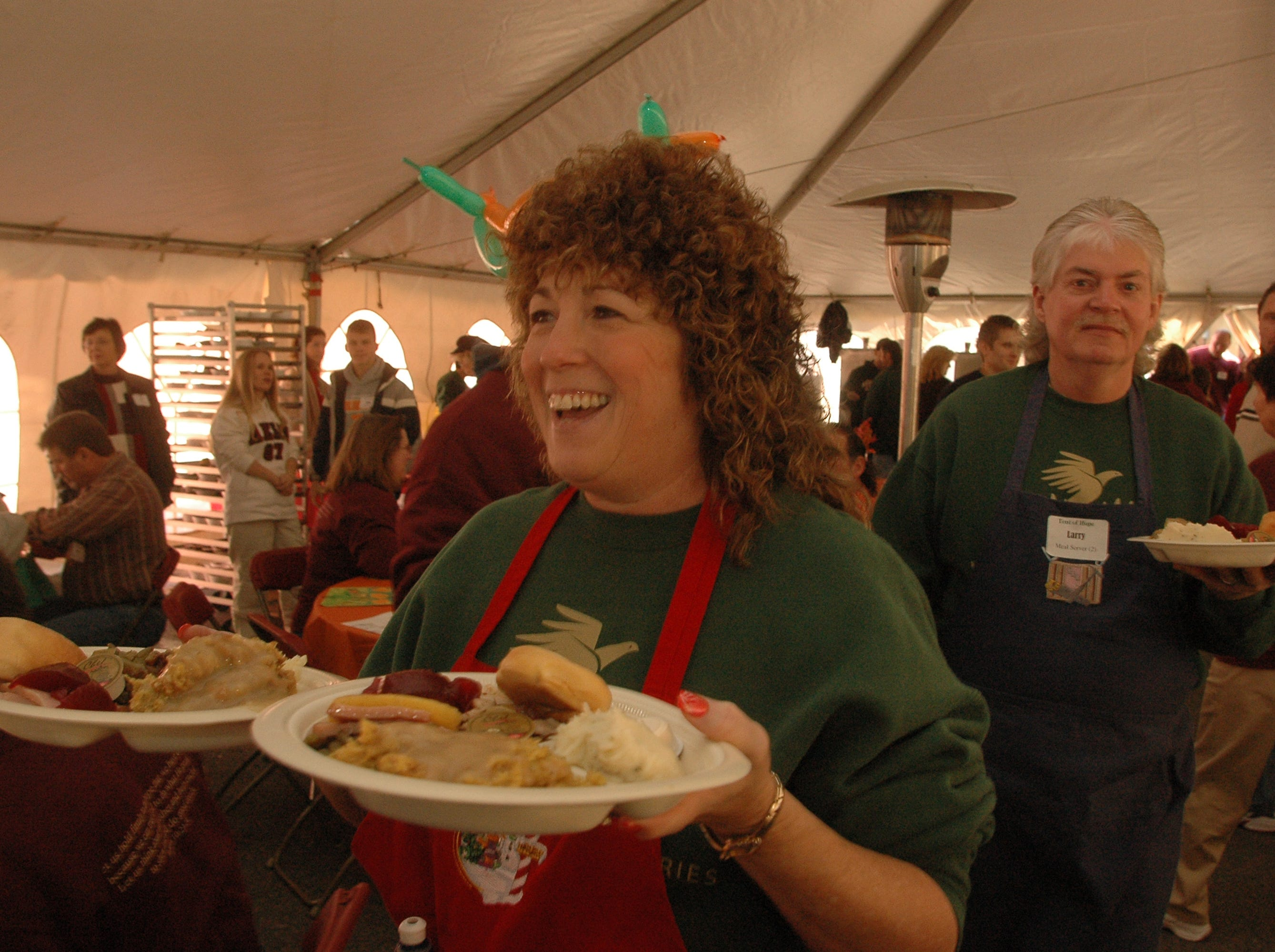"""Volunteers Sharon Bender (left) and Larry Cotter both of Clinton spent part of their Thanksgiving Day help serve meals at the annual Knox Area Rescue Ministries """"Tent of Hope."""" Dozens of Volunteers gathered at  Knoxville Area Rescue Ministries on Thanksgiving Day to help feed the homeless and less fortunate in Knoxville.   November 24, 2005"""