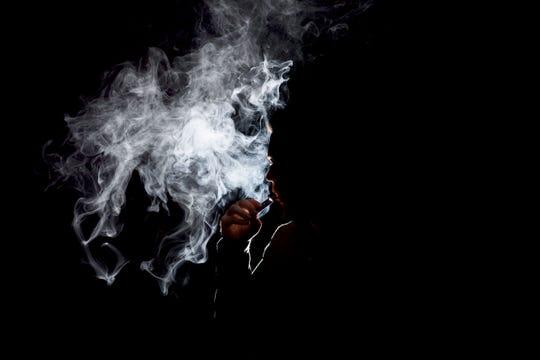 A figure smokes a Juul e-cigarette.