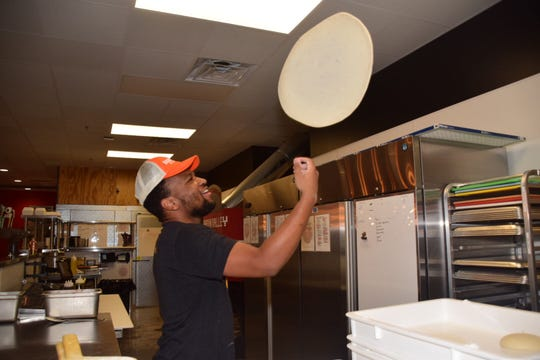 Quanelo Evans, kitchen manager, tosses dough high into the air at Hard Knox Pizza 10849 Hardin Valley Road Wednesday, Nov. 14.