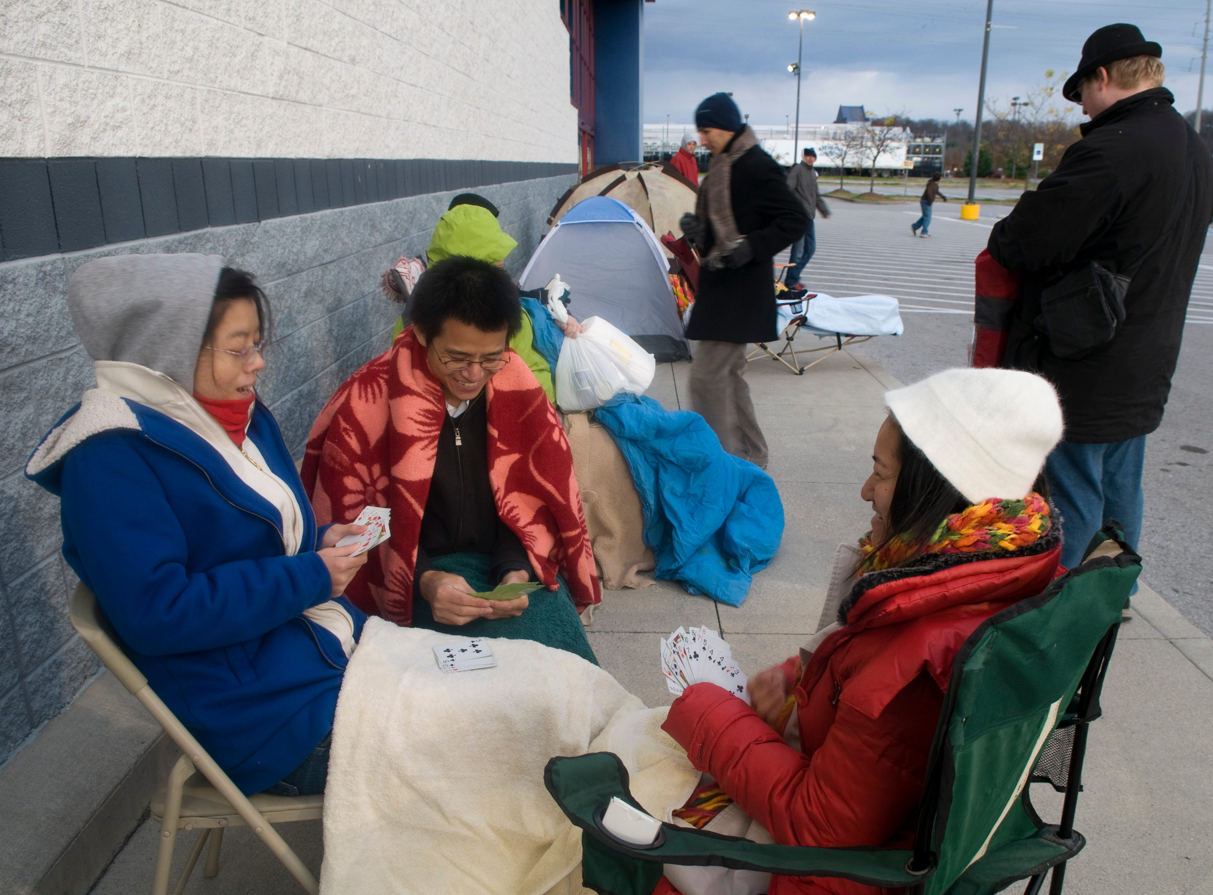 Three UT students play a game of cards to pass the time as they wait for Best Buy to open Friday morning.   Cai Quing, left, Hu Zhixiong, (cq) center and Minfeng Jin, right are UT students and they are waiting to buy a computer. Early bird shoppers started lining up outside Knoxville Store before the sun set on Thanksgiving Day. Thursday, November 26, 2009
