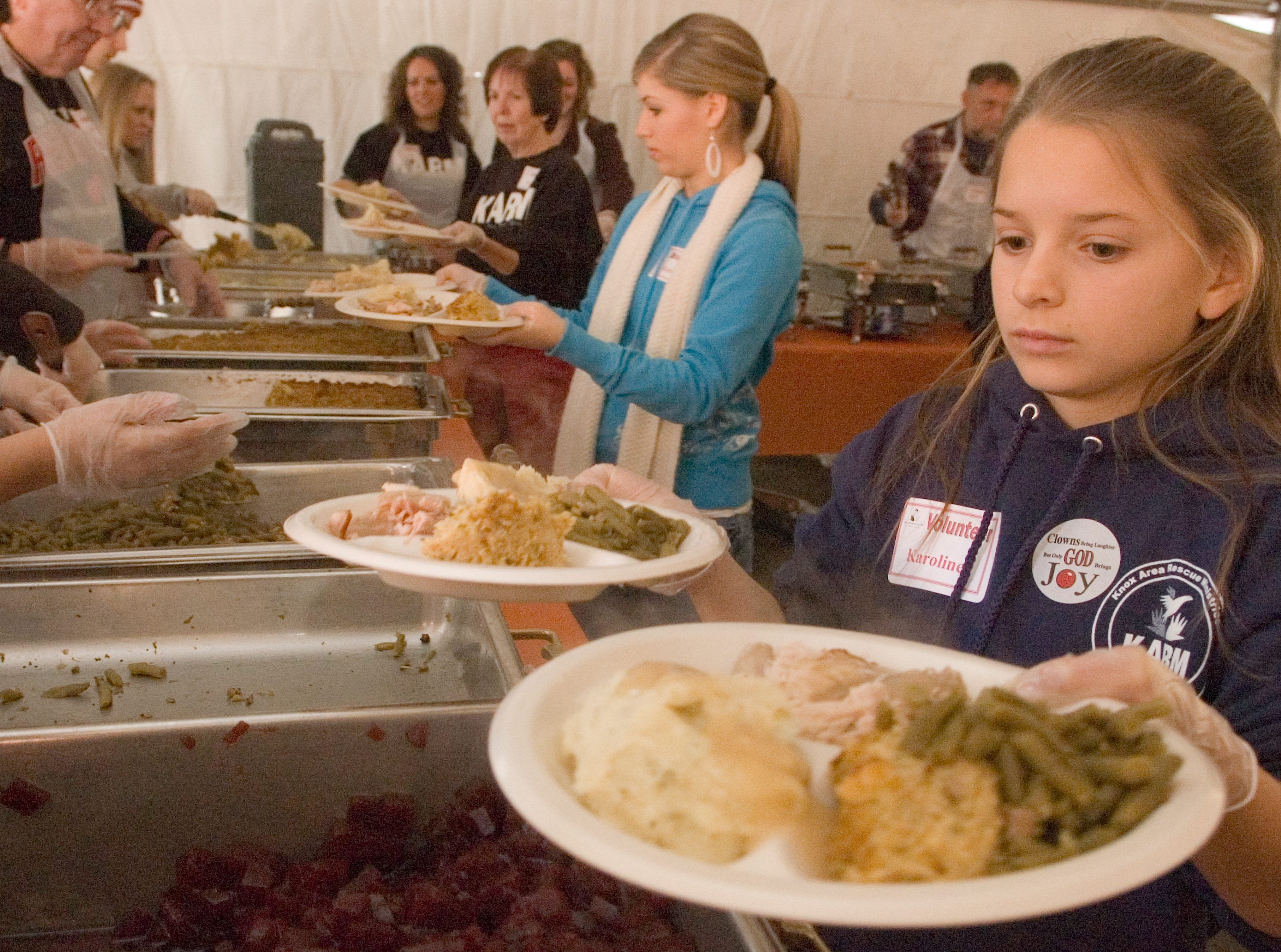 Karoline  Barnett, 10, right, and her sister Kate Barnett, 17, center move down the serving line gathering plates of food at the Annual Knox Area Rescue Ministries Thanksgiving Tent of hope meal.  Thursday, November 27, 2008