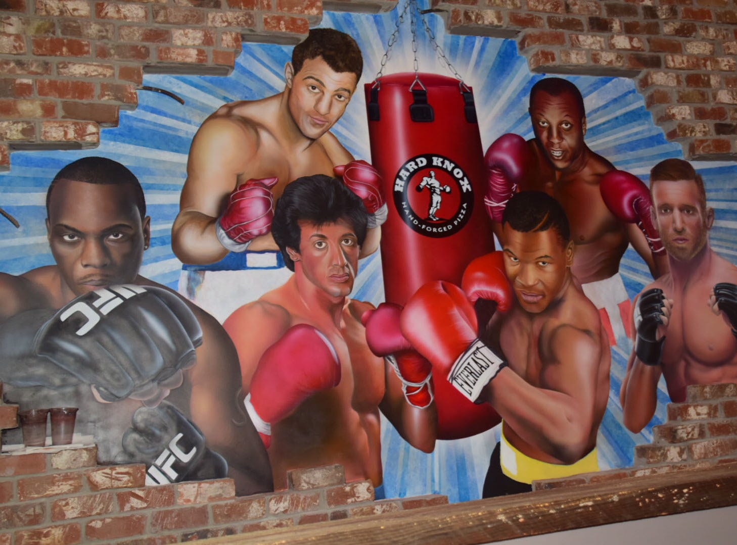 A mural depicting famous boxers is underway at Hard Knox Pizza. Each pizza is named after a boxer.