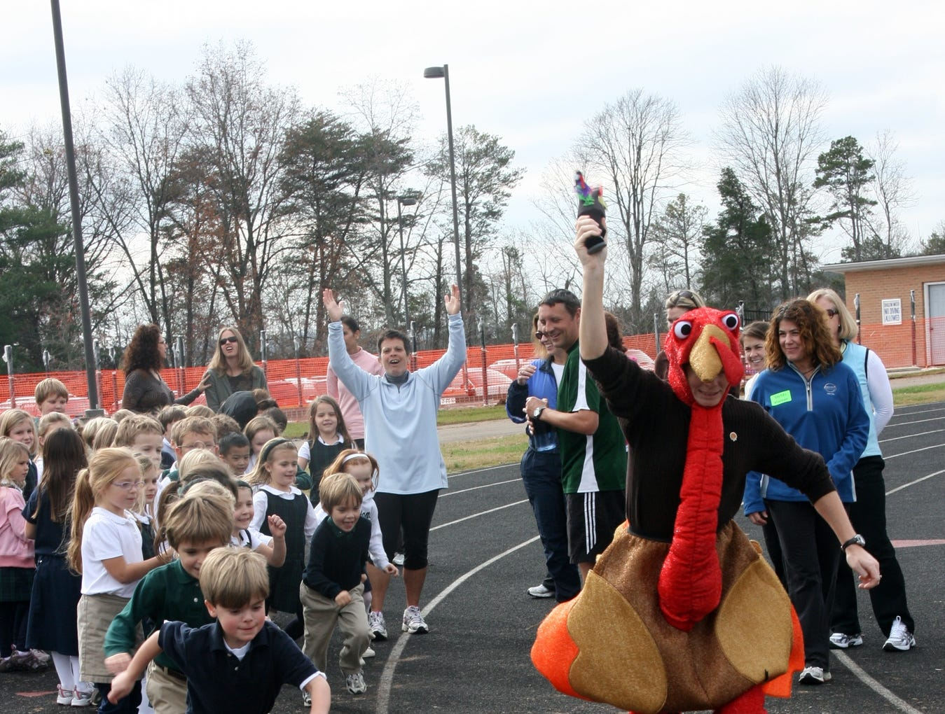 """The """"Thanksgiving Turkey"""", Camp Webb summer camp director Allison Hodges, gives the """"go"""" signal to Webb's kindergarten students for their Turkey Trot around Webb's Faust Field track. Turkey Trot participants brought in canned food items for Second Harvest Food Bank of East Tennessee."""