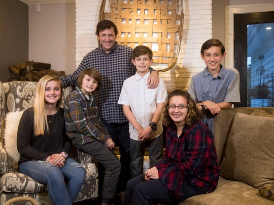 Simon Hall poses with five of his six adopted children, Abby, Mason, Blake, Lexi and Nicholas, at their home Monday, Nov. 5, 2018.