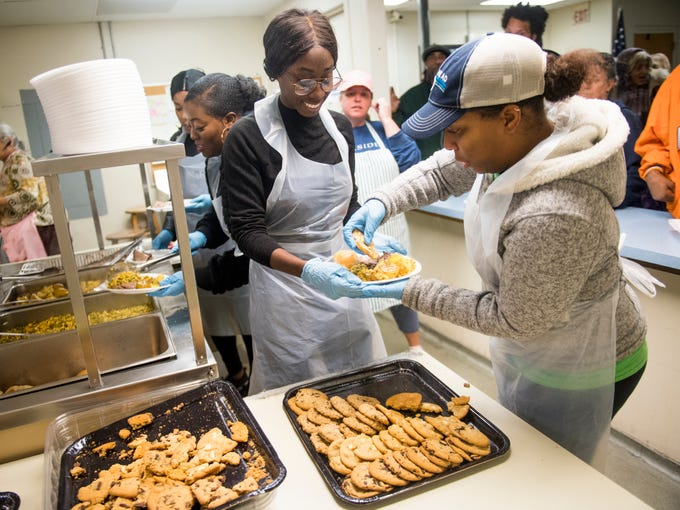 Melody Boafo, left, and Kara Demonbreun, right, Phi Delta Epsilon medical fraternity members from Ross University School of Medicine, prepare a plate of food together at The Love Kitchen in Knoxville on Wednesday, November 14, 2018.