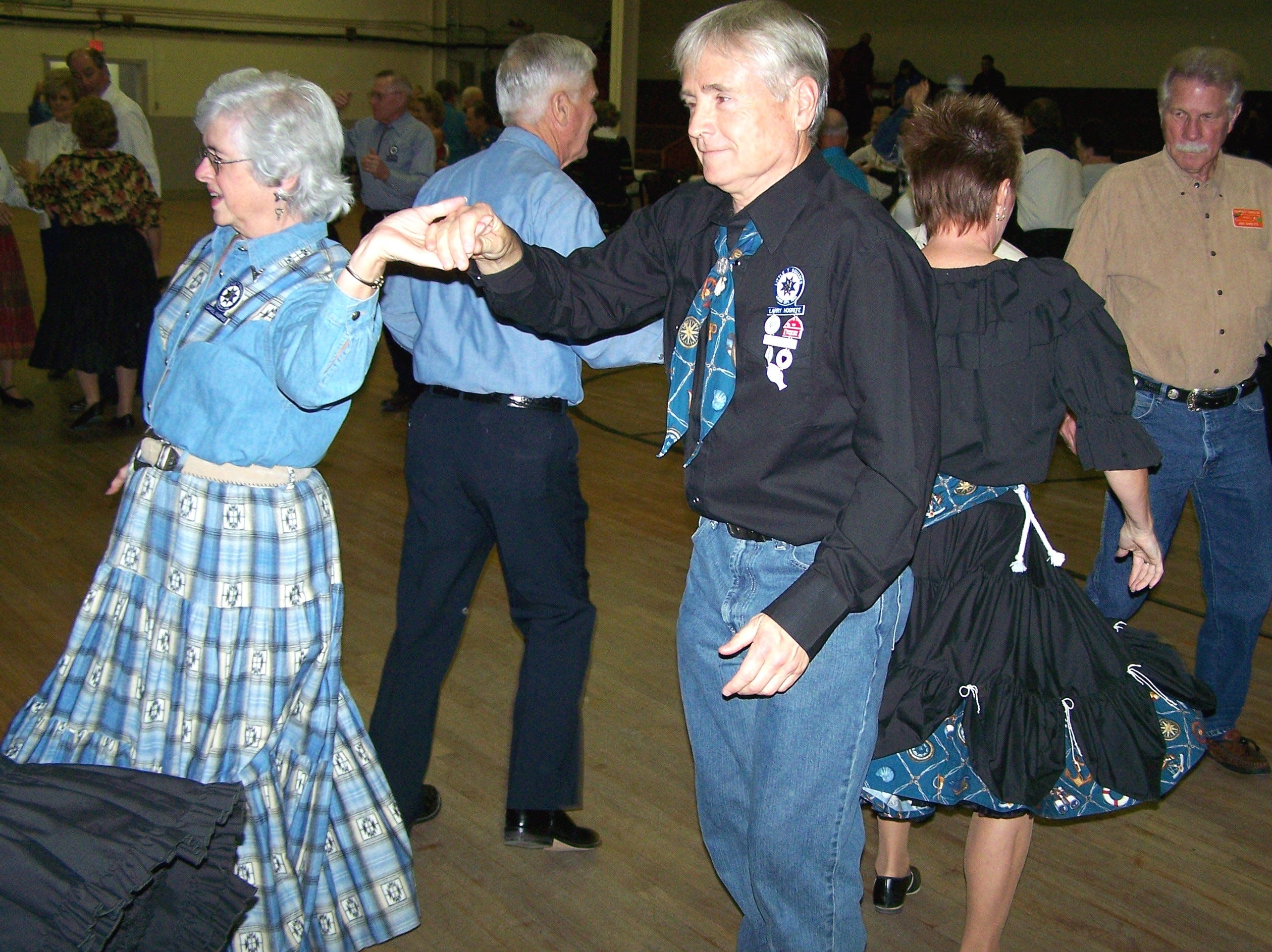 Little T Squares dancers Carol McBride and Larry Hogrefe execute a 'partner trade' maneuver during the Thanksgiving dinner and dance.