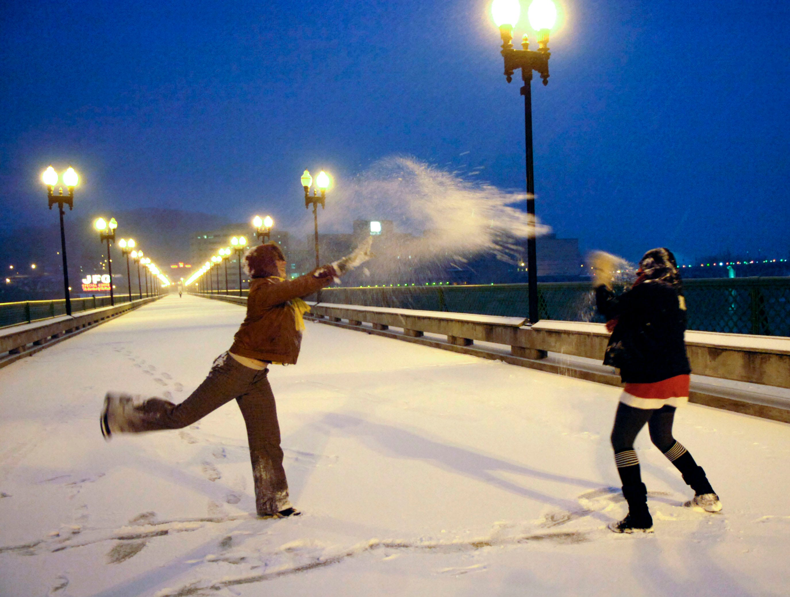 "Katherine Campbell tosses a snowball at her friend Heather Nijoli (cq) on the Gay Street Bridge in downtown Knoxville on Thursday, Jan. 7, 2010. ""It's so cool, I love the city and I love what it looks like in the snow."" says Nijoli. The friends met on the bridge, which was closed to traffic due to weather conditions, to enjoy the snow."