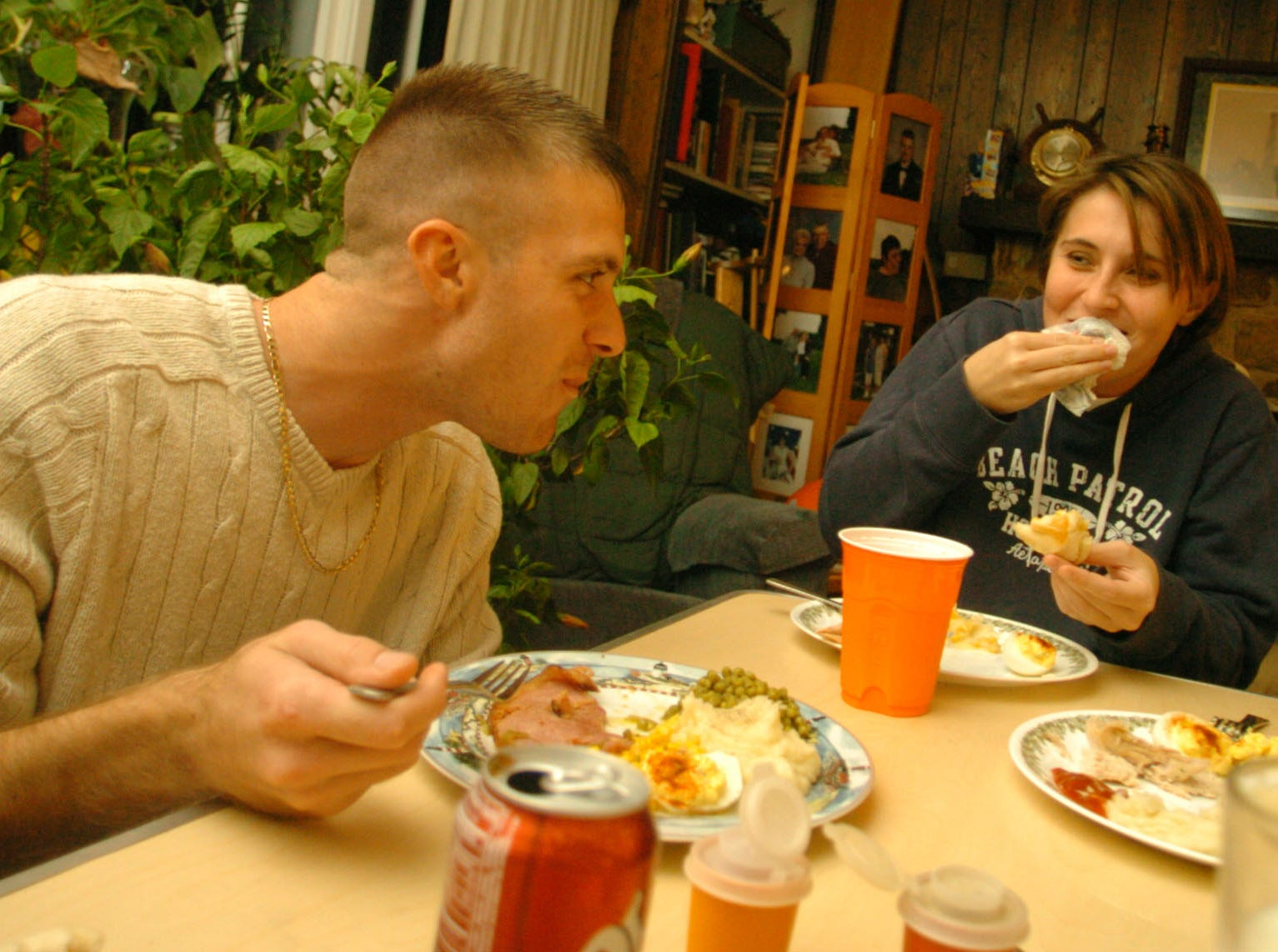 Marine Sgt. Joey Valentine, left, having Thanksgiving dinner with girlfriend Misty Moore, center, and older brother Marine Sgt. Wayne Valentine. Joey has already been overseas and has returned, Wayne will be deployed in January. 2004