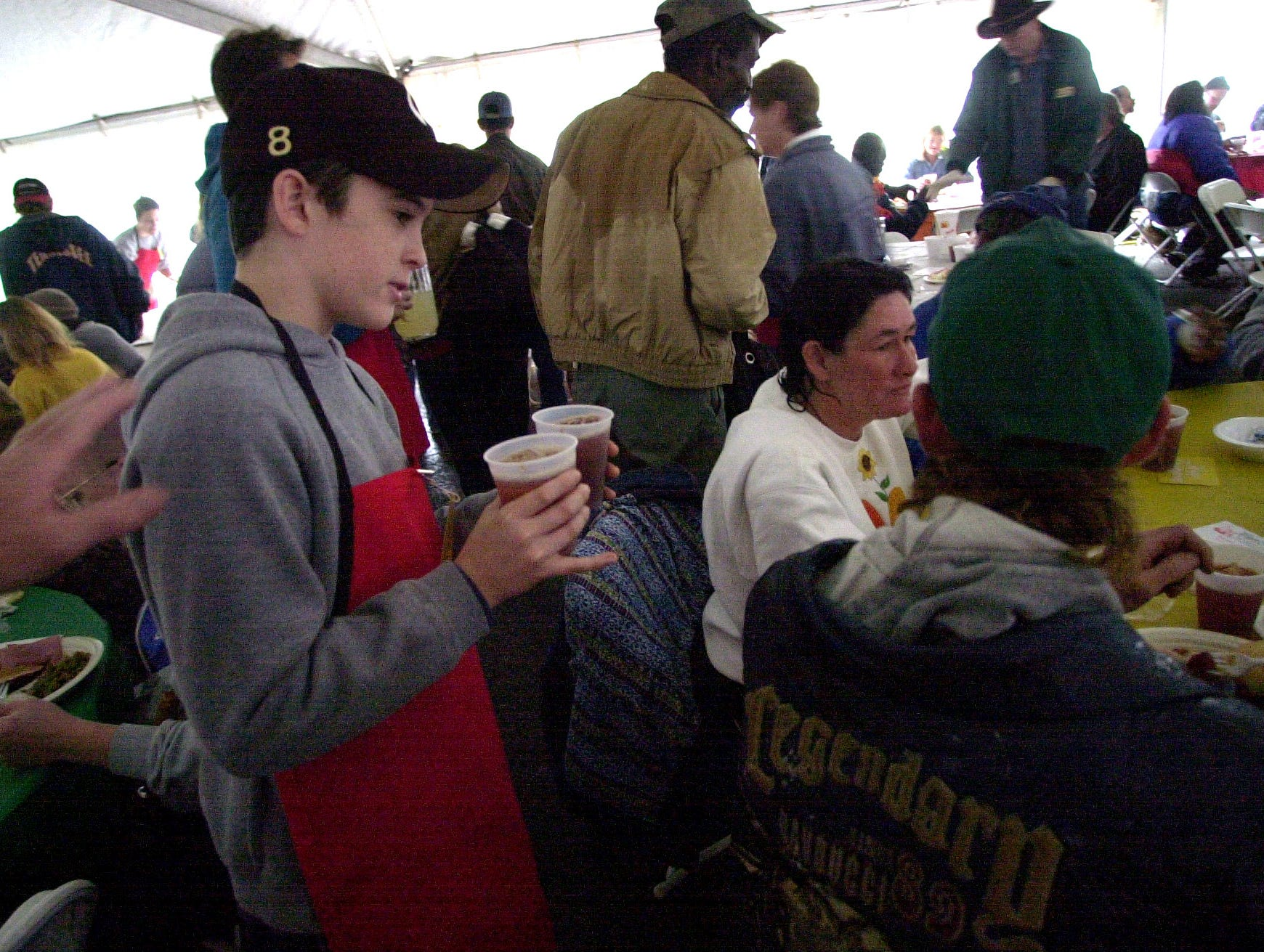 Justin Hobby passes out drinks as a volunteer during the Knoxville Area Rescue Ministries annual Thanksgiving Day meal.