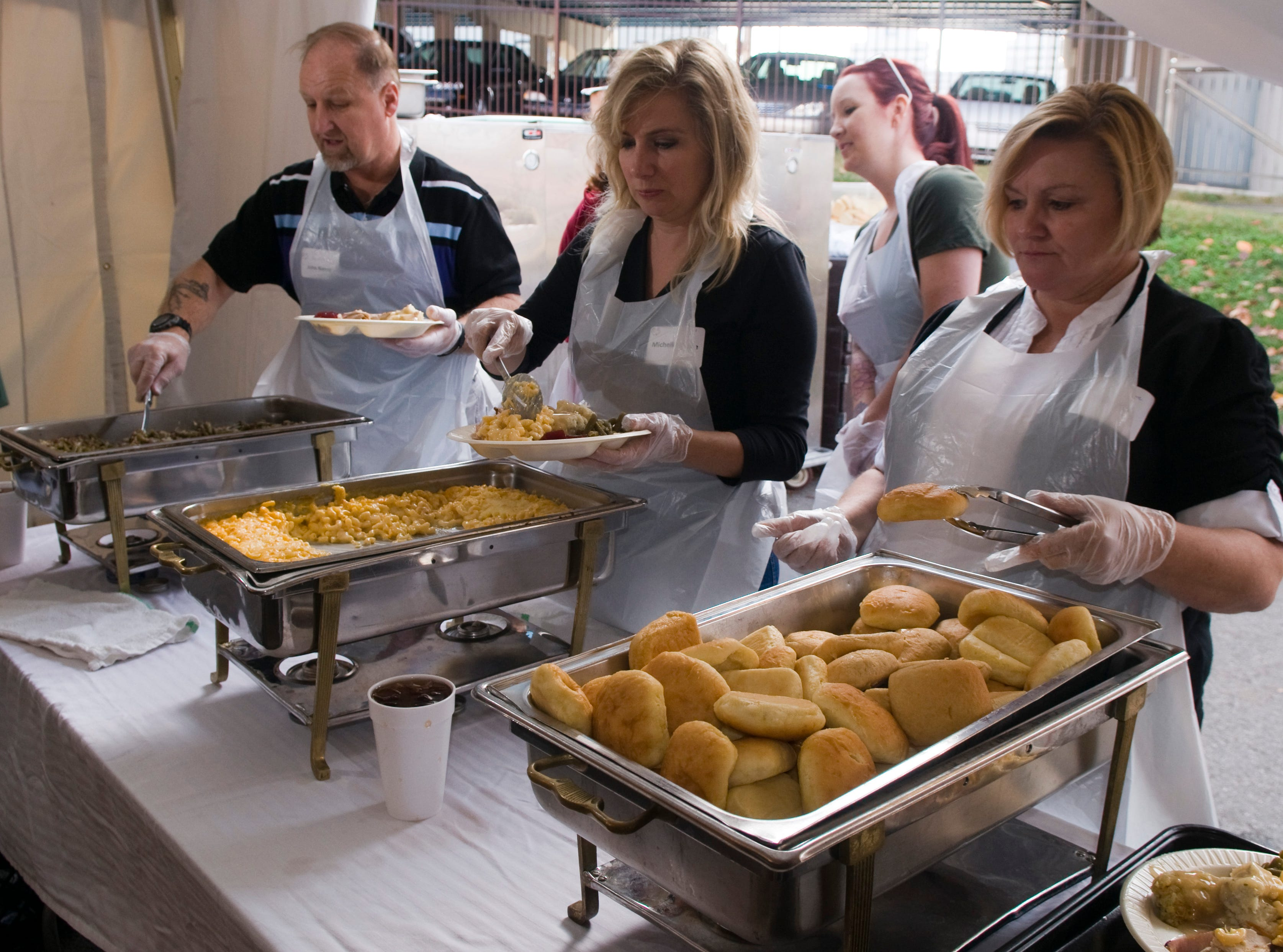 Volunteers load pates of food of the Thanksgiving dinner at the KARM Tent of Hope Thursday morning.  John Nance, left,  has the green beans, Michelle Hunley, center, has the mac and cheese and Toni Hall, right watches over the rolls.