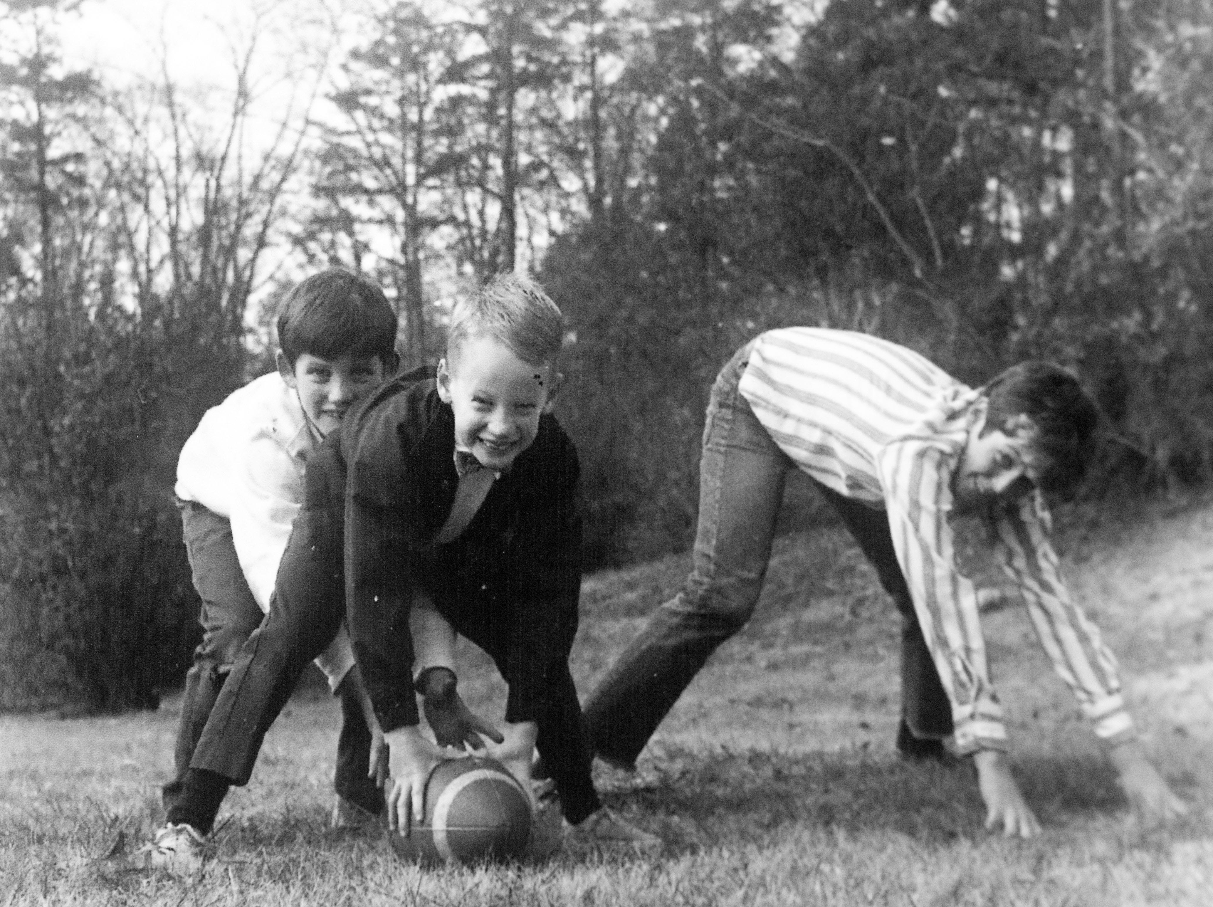 Youths play football outside the Willard home during Thanksgiving in 1977.