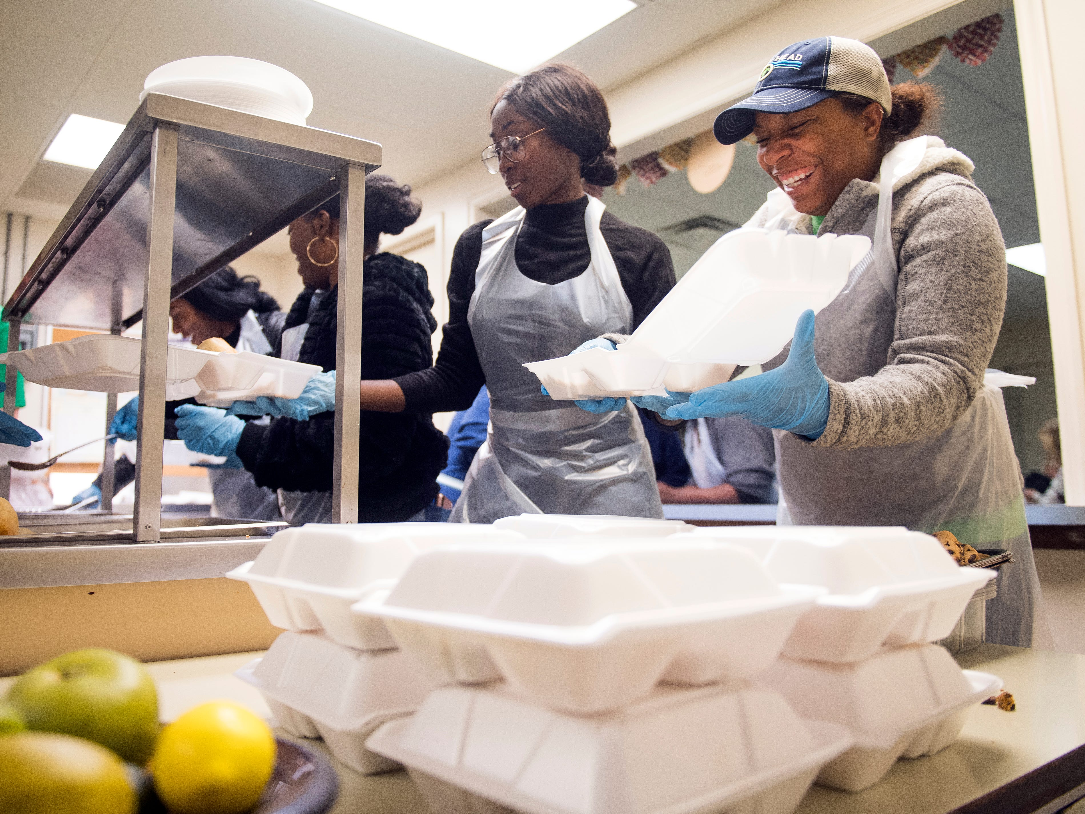 Kara Demonbreun, right, laughs as she helps prepare to-go boxes of food at The Love Kitchen in Knoxville on Wednesday, November 14, 2018. Demonbreun and multiple other Phi Delta Epsilon medical fraternity members from Ross University School of Medicine spent the afternoon volunteering at The Love Kitchen.