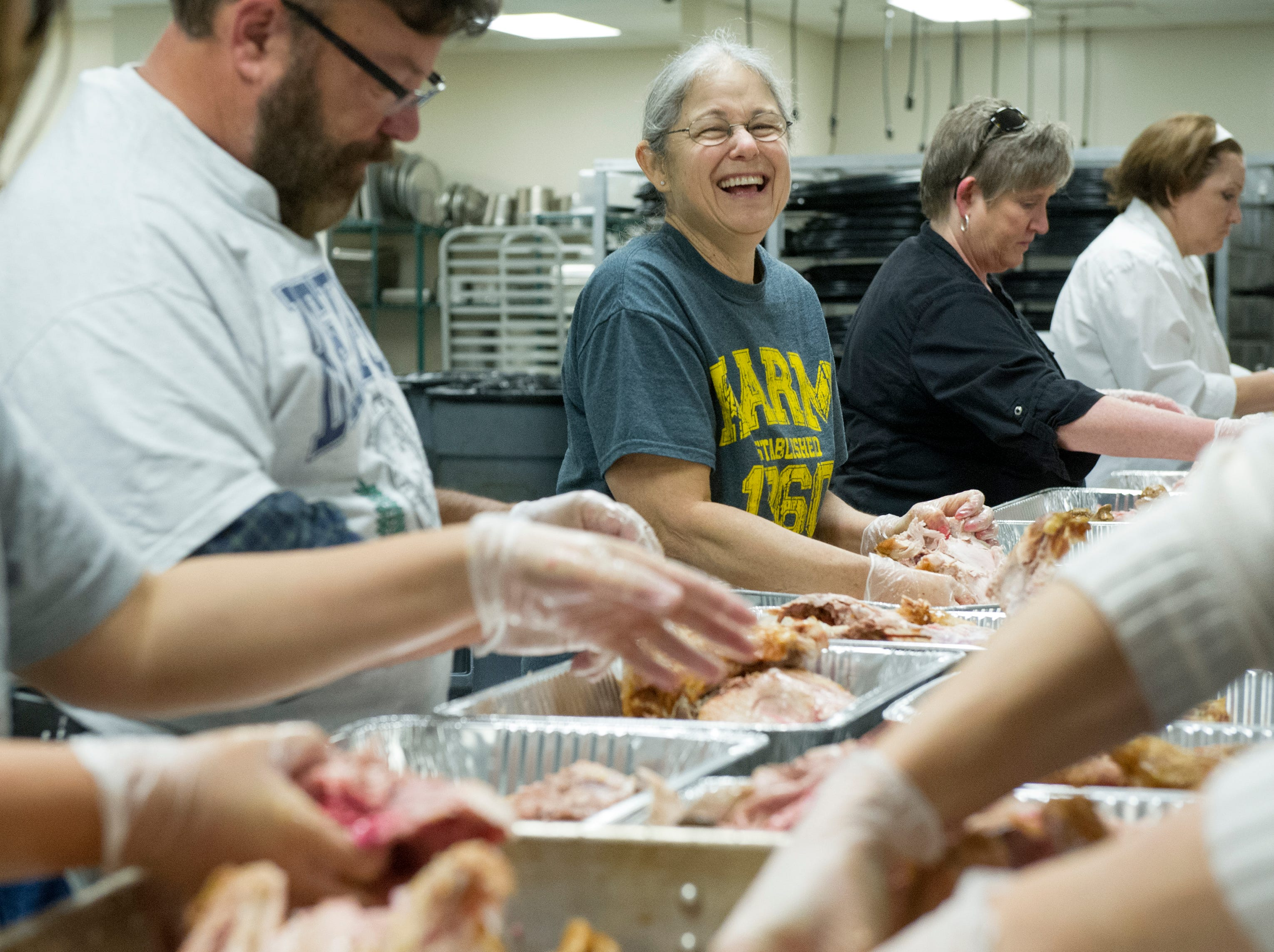 KARM volunteer Carolyn Rosen (center) enjoys the company of her fellow volunteers during the preparation of 100 turkeys for KARM's Thanksgiving meal at the Knoxville Convention Center Saturday, Nov. 21, 2015.