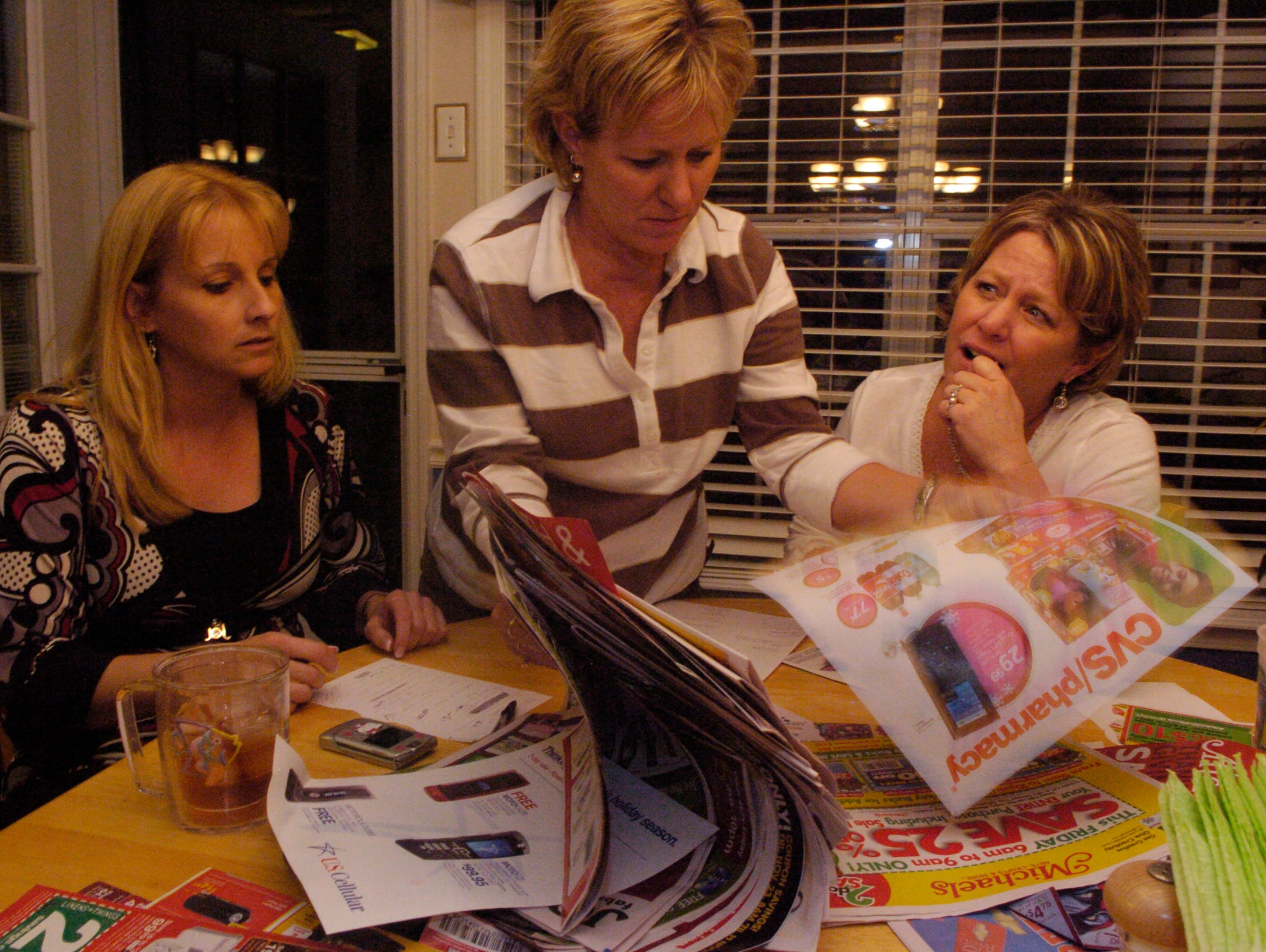 From left, Sheila Menning, Sondra Day and her twin sister, Ronda Coomer, read Thanksgiving day newspaper ads on Thursday. The women are planning the annual Morgan family Black Friday shopping trip.