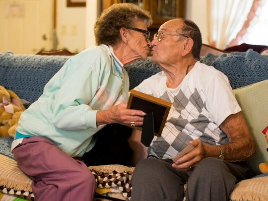 Phil Candia, left, leans in to kiss her husband Whorley Candia, right, at their home in Newport on Friday, November 2, 2018.