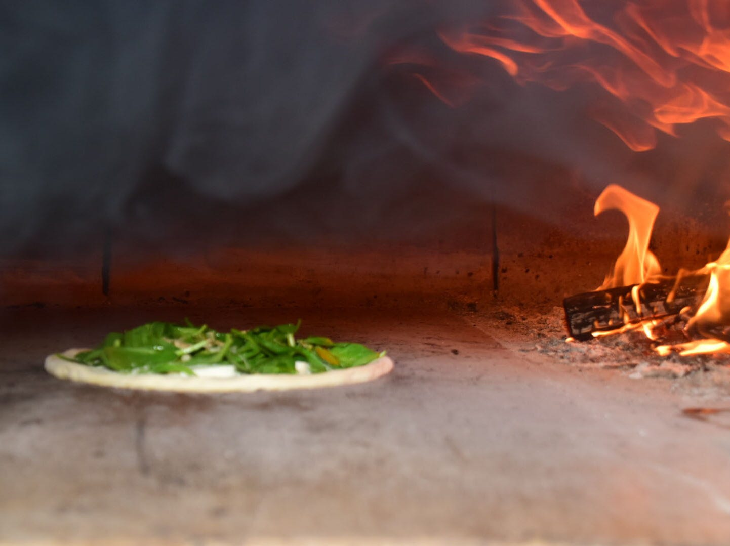 The Iron Mike pizza being baked close to flames features spinach, fresh mozzarella, and shaved parmesan cheese at Hard Knox Pizza.