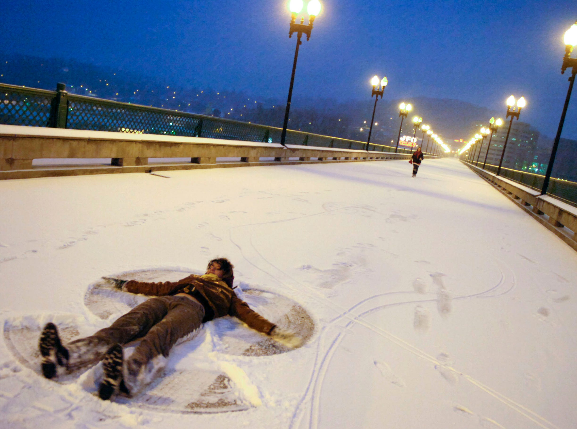"Katherine Campbell makes a snow angel lying in the middle of the Gay Street Bridge as her friend Heather Nijoli runs toward her in downtown Knoxville on Thursday, Jan. 7, 2010. ""It's so cool, I love the city and I love what it looks like in the snow."" says Nijoli. The friends met on the bridge, which was closed to traffic due to weather conditions, to enjoy the snow."