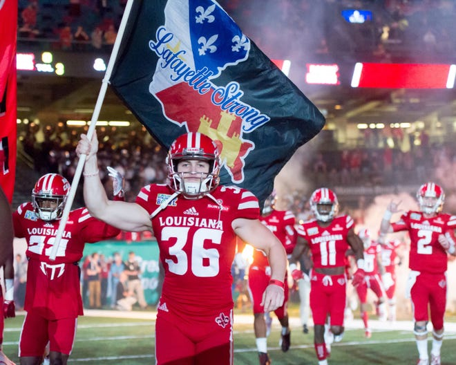 Kicker Stevie Artigue, out this year following offseason ACL surgery, leads UL onto the field at the Superdome prior to its 2016 New Orleans Bowl game against Southern Mississippi. The Ragin' Cajuns can get bowl-eligible with a win Saturday over South Alabama.