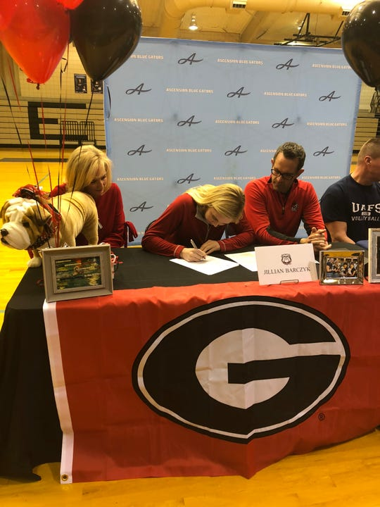 Ascension's Jillian Barczyk signs her national letter of intent with seven-time national champion Georgia on Friday with her parents Colleen and David Barczyk joining her.