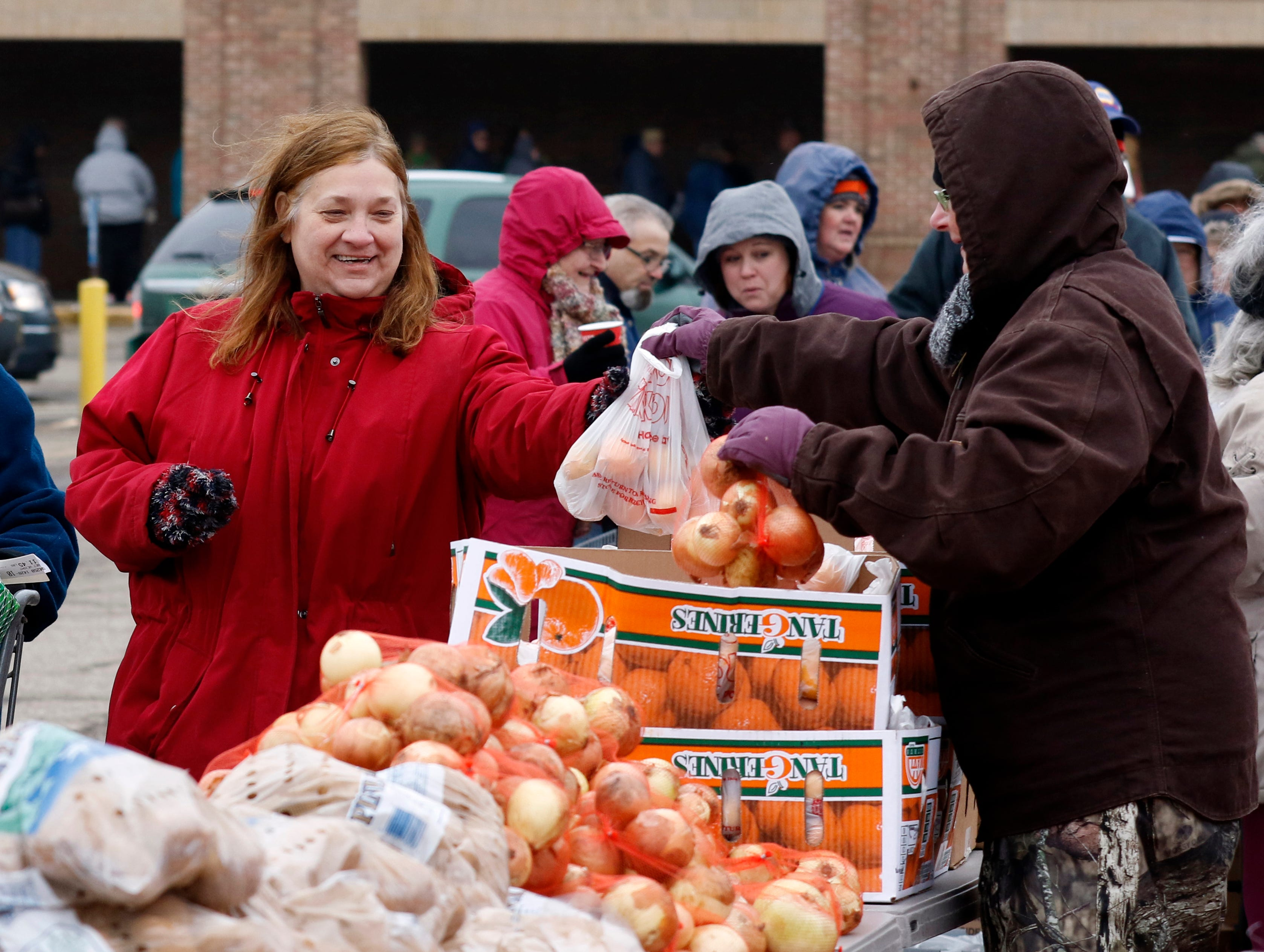 Theresa Johnson, left, accepts a bag of apples from Sally Grimm Thursday, Nov. 16, 2018, as Johnson goes through the line to receive the items to prepare a Thanksgiving dinner on East Main Street in Lancaster. Johnson was one of about 500 Lutheran Social Services Food Pantry clients to receive a Thanksgiving meal Friday.