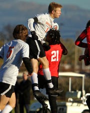 Charlie Sharp (8) elevates over Grand Blanc's Muaz Asperger (21) in Brighton's 2-1 regional semifinal loss on Tuesday, Oct. 23, 2018.