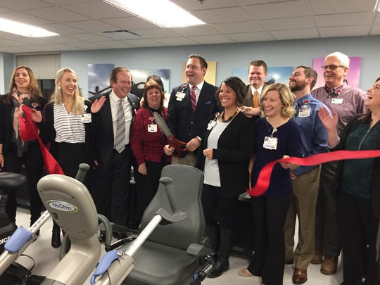 Bryan Foster, St. Joseph Mercy Livingston's cardiac rehab manager, center, performs a ribbon cutting surrounded by staff and hospital administrators, Thursday, Nov. 15, 2018.