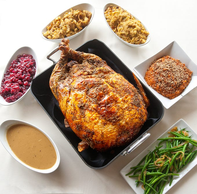Varanese restaurant owner and executive chef John Varanese's turducken, a chicken stuffed in a duck stuffed in a turkey, surrounded by accompaniments, clockwise from bottom left: turducken gravy, bourbon cranberry chutney, traditional pork sausage stuffing, corn bread and sage stuffing pecan crumble-topped Amaretto sweet potato casserole and a side of green beans and onions. November 14, 2018