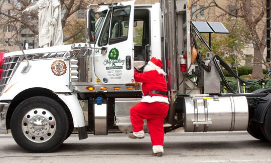 Chip Trucking driver Mike Corner, dressed as Santa, steps down from his truck cab after arriving at Jefferson Square Park with this year's Christmas tree.