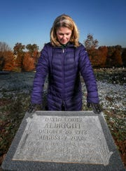 Jennifer Albright stands at Calvary Cemetery at the grave where her husband and her son are both buried.