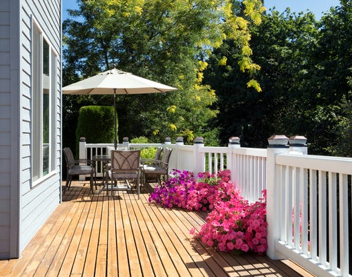 Home Cedar Deck During Bright Summer Day With Blooming Garden Of Flowers