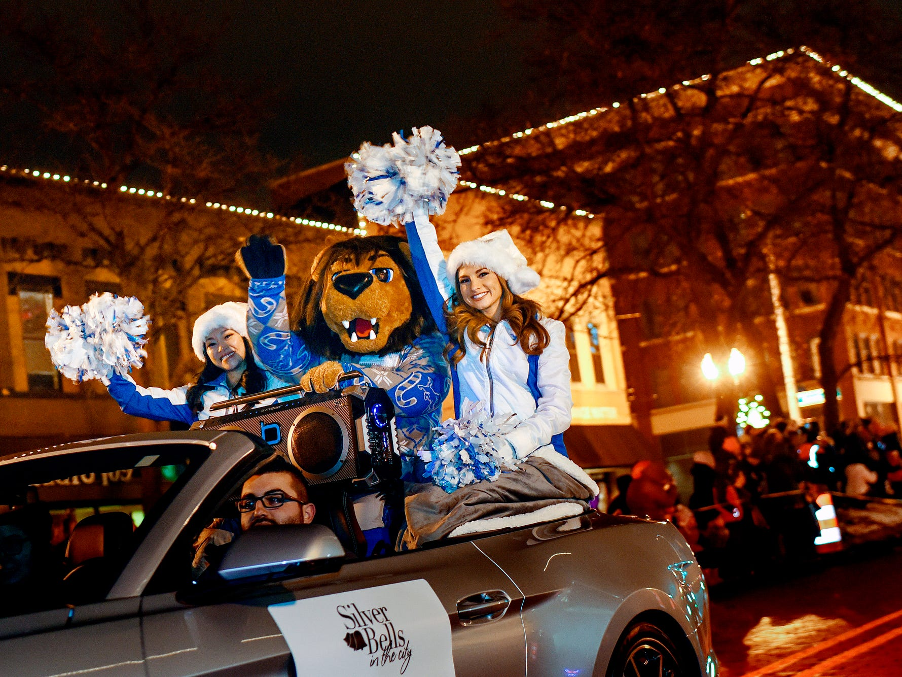 Detroit Lions mascot Roary and two cheerleaders wave to the crowd as they ride in the Silver Bells in the City Electric Light Parade on Friday, Nov. 16, 2018, in downtown Lansing. They were selected as Grand Marshals of the parade.