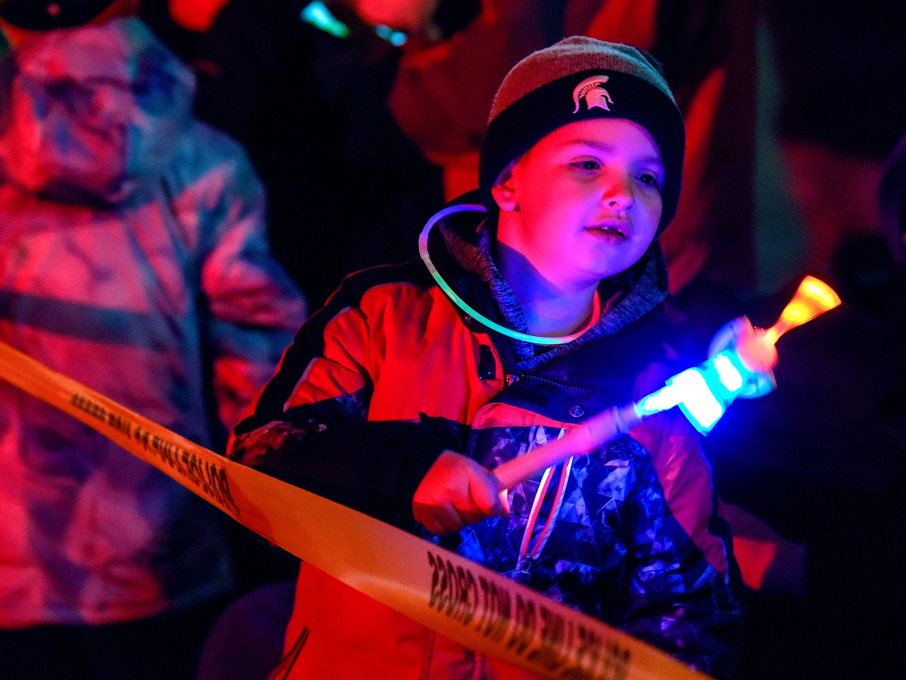 DeWitt resident Gavin Wethy, 5, plays with a light stick while waiting for the Electric Light Parade to start during Silver Bells in the City on Friday, Nov. 16, 2018, in downtown Lansing.