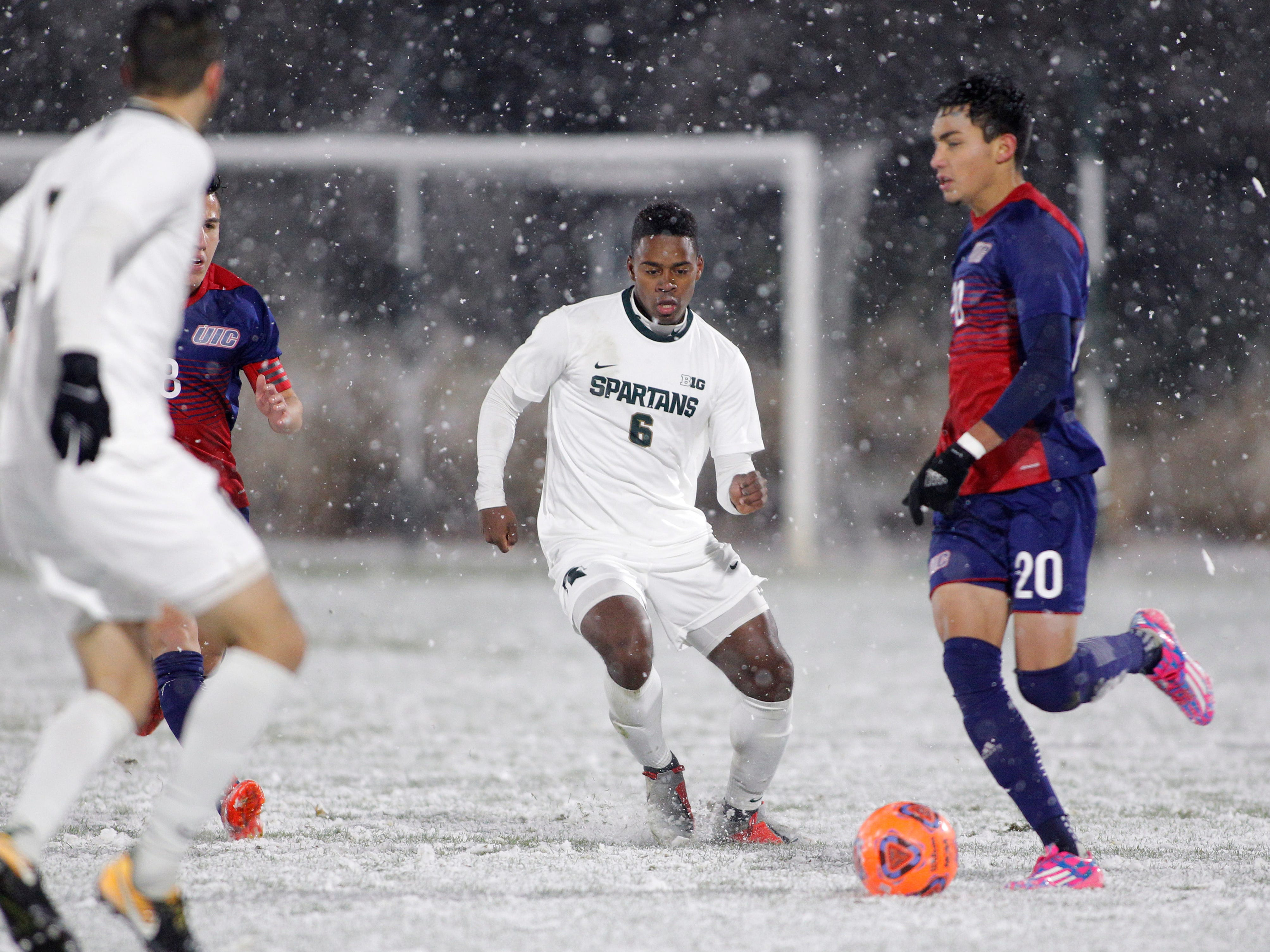 Michigan State's DeJuan Jones (6) passes the ball against Illinois-Chicago's Eduardo Garcia (20) and Oscar Gonzalez, left, during their NCAA first round game, Thursday, Nov. 15, 2018, at DeMartin Stadium in East Lansing, Mich. MSU won 2-0.
